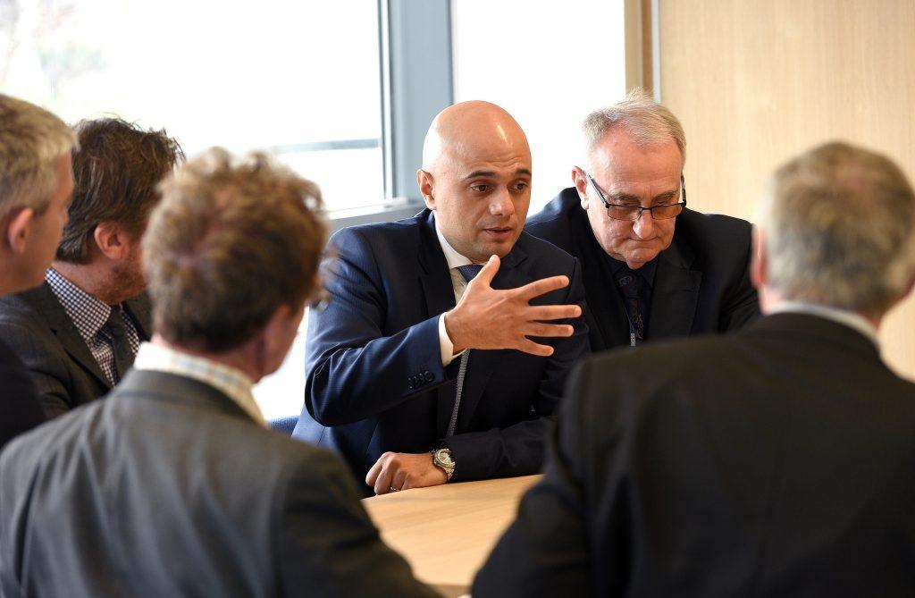 Sajid Javid speaks in a group of men