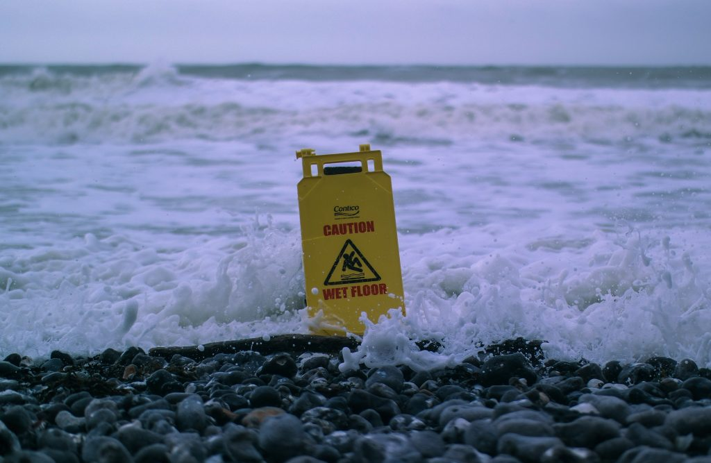 caution wet floor sign in the sea