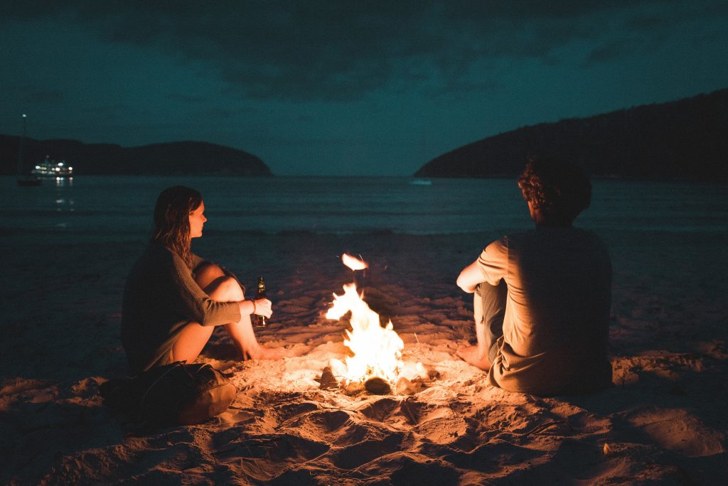 couple sitting on a beach in the dark