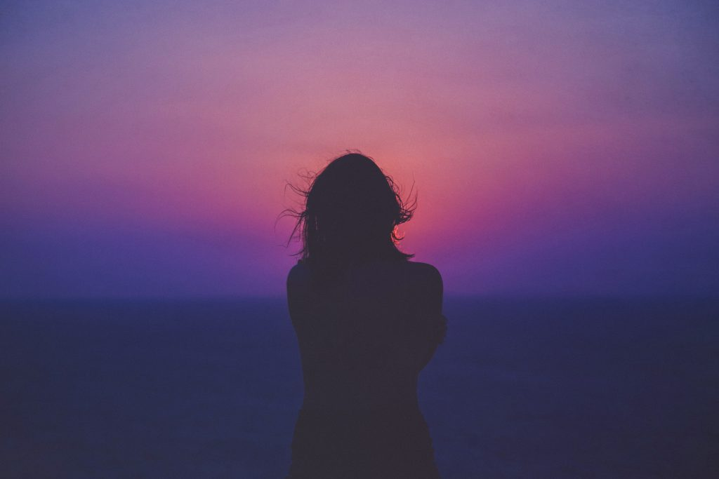 a woman looks out on a purple sunset