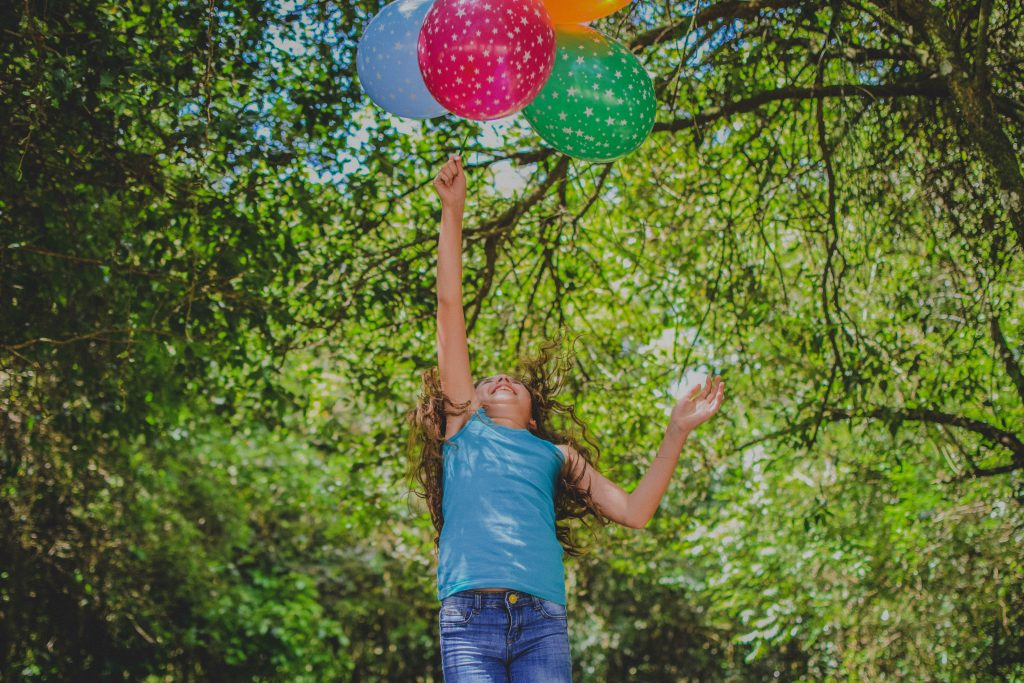 a girl playing with baloons to signify the right to play