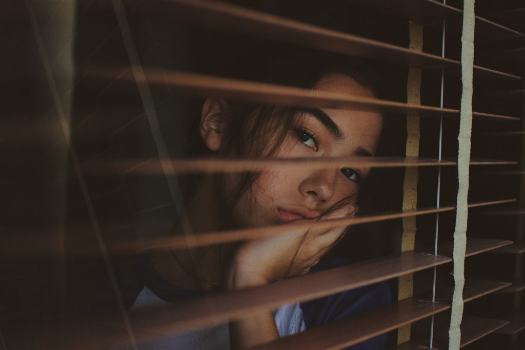 Sad girl looking out of blinds