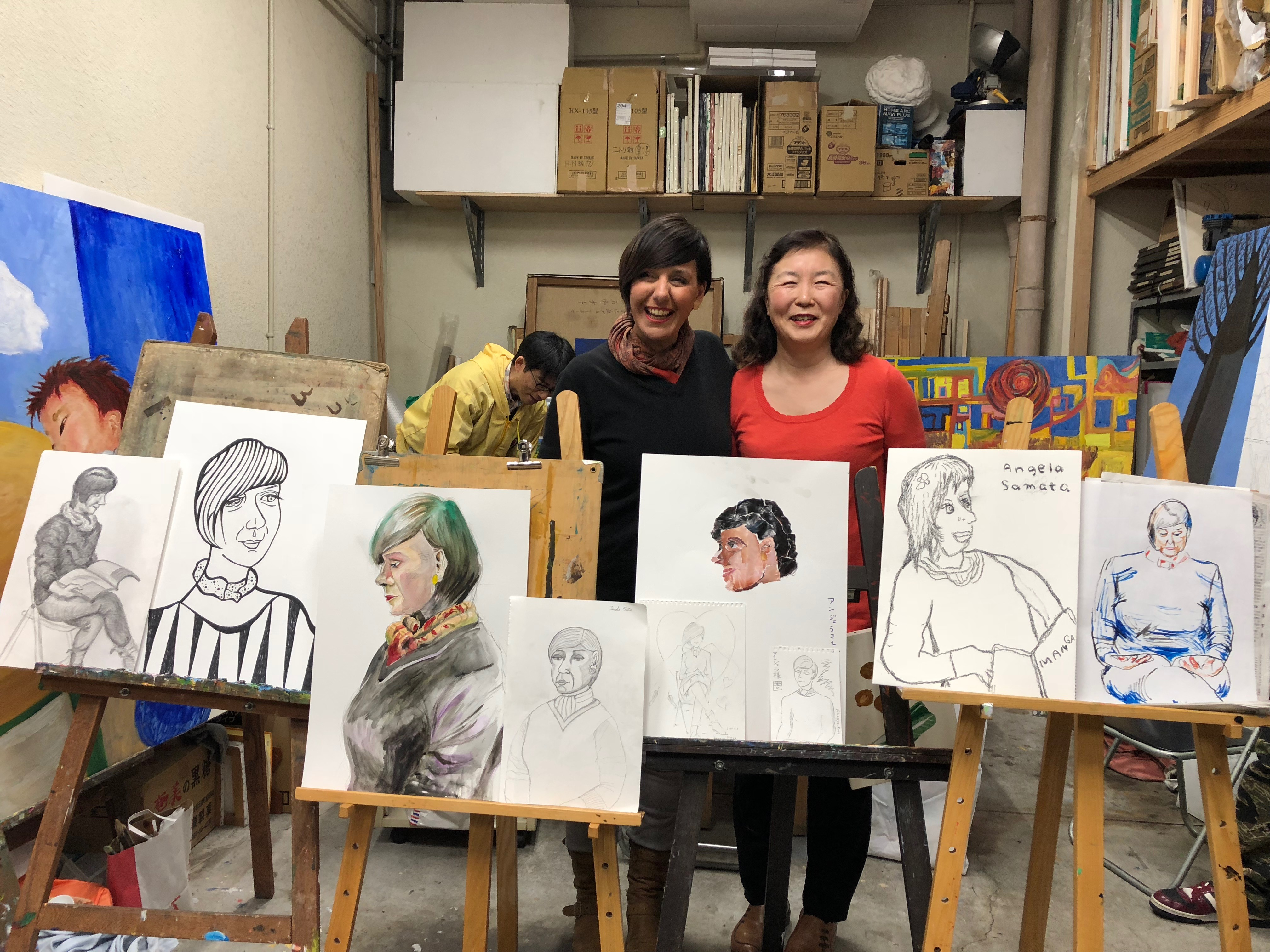 Two women are standing in an art workshop surrounded by easels and canvases. All the pictures and paintings are of Angela Samata who is on the left of the photo.