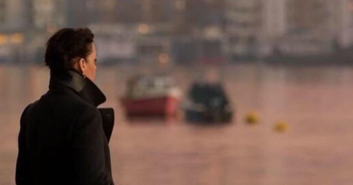 A woman in a black coat looks across a harbour, there are boats in the background