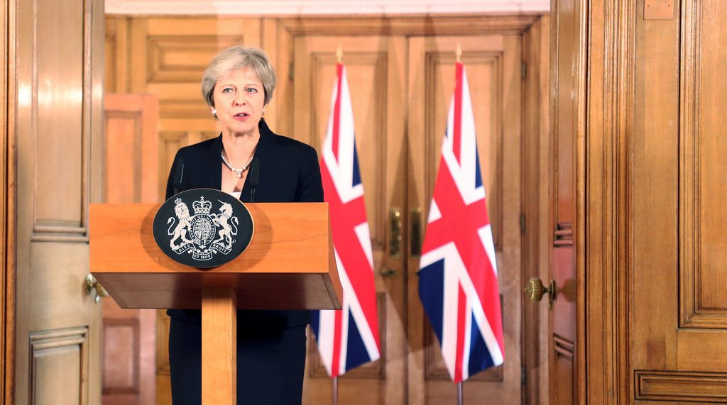 Theresa May, British PM, at a podium in front of two British flags