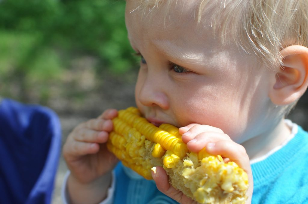 A child eats some sweetcorn