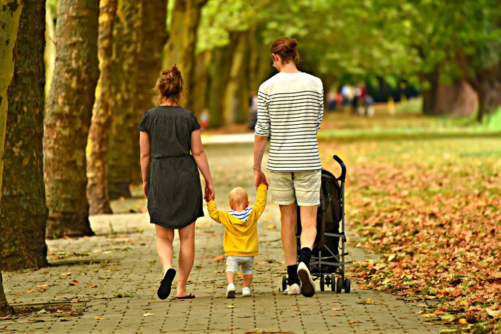 Two parents walk with their child