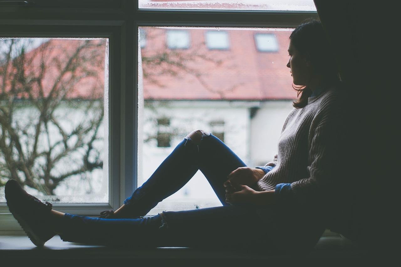 Woman looks outside of window