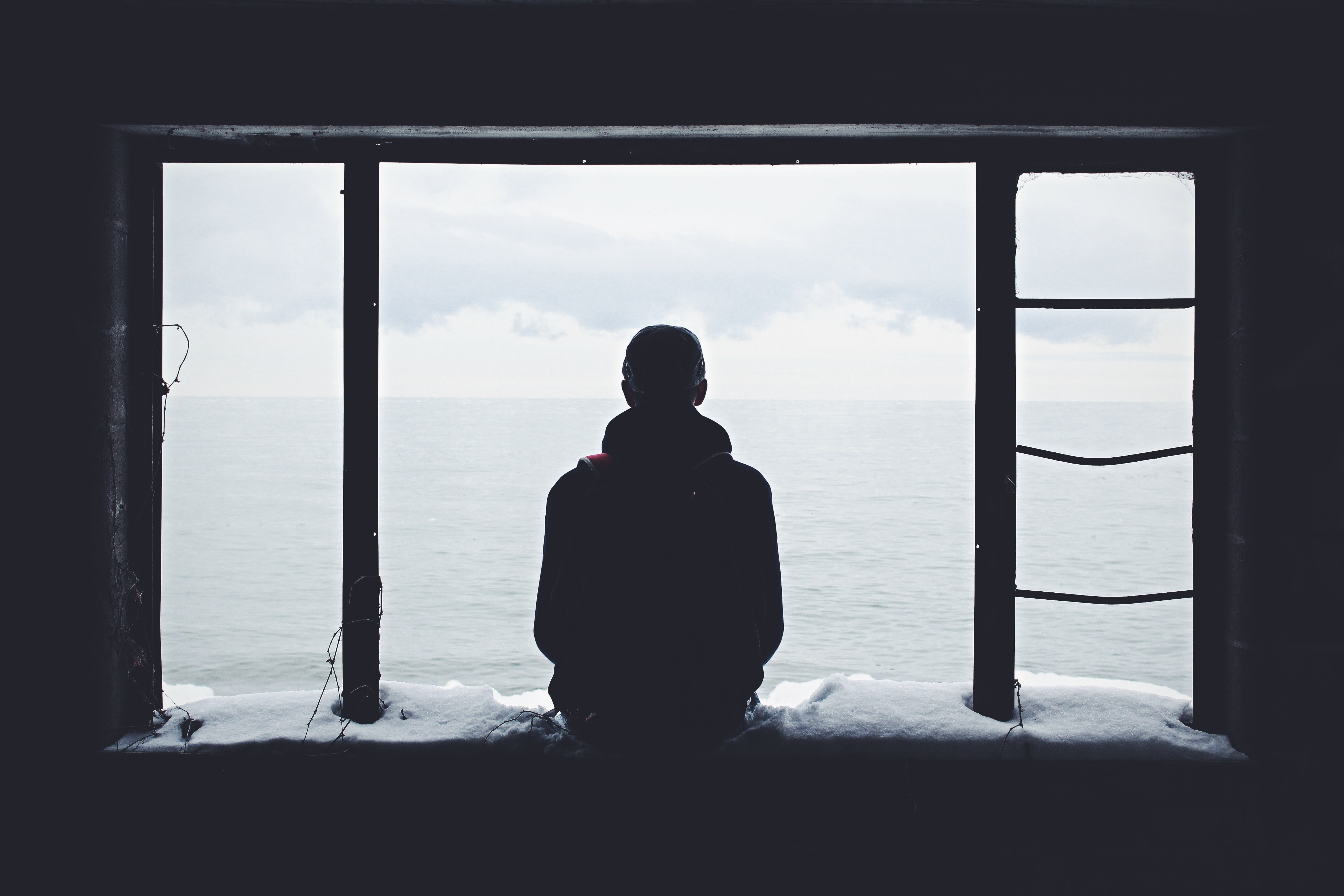 The silhouette of a person looking out of a window.