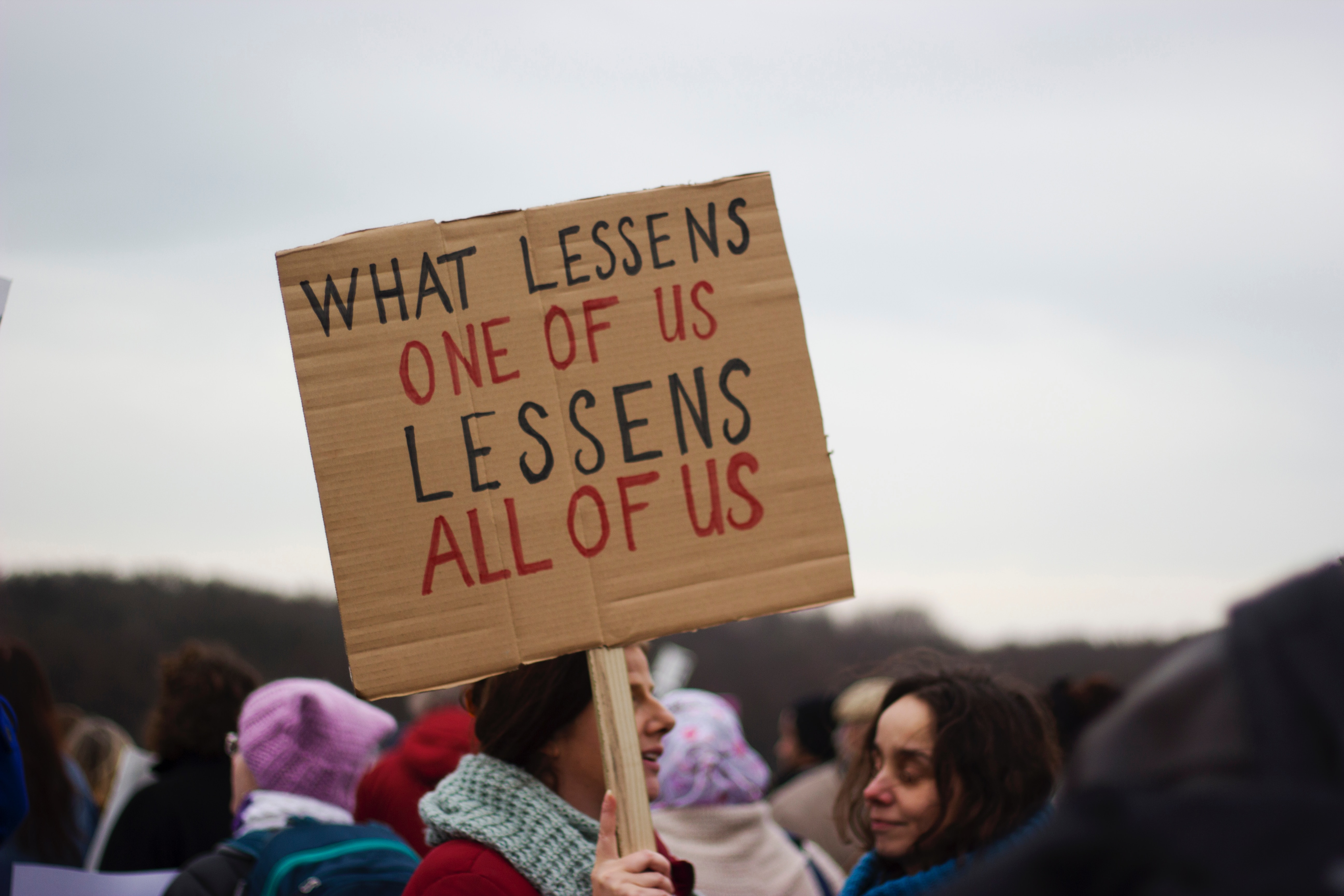 "A protestor holds a sign saying ""what lessens one of us, lessens all of us"""