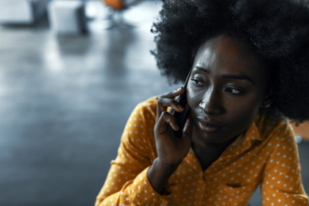 Young black woman in yellow shirt with anxious expression on her phone.