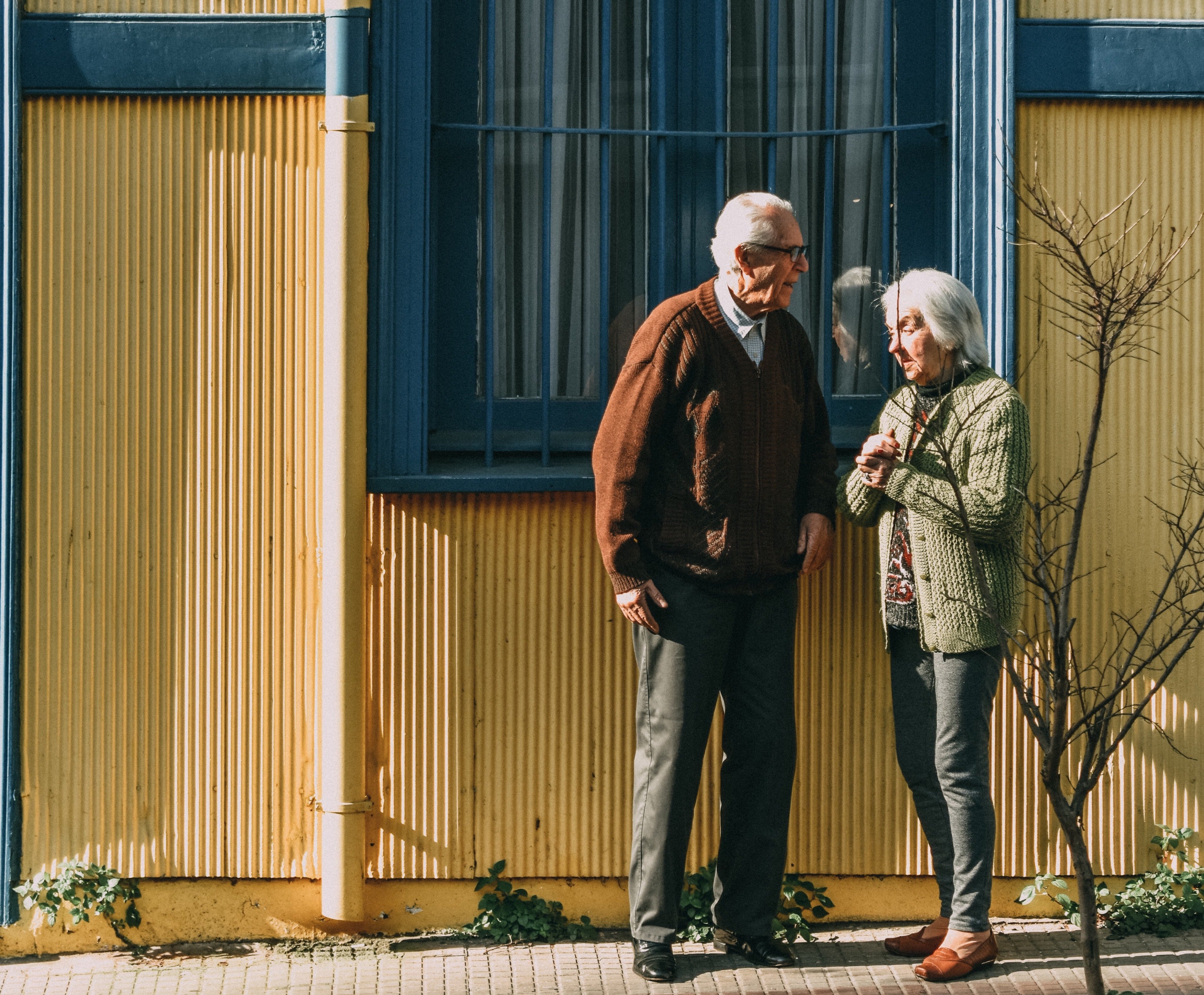 An older man and woman stand in front of buildings window