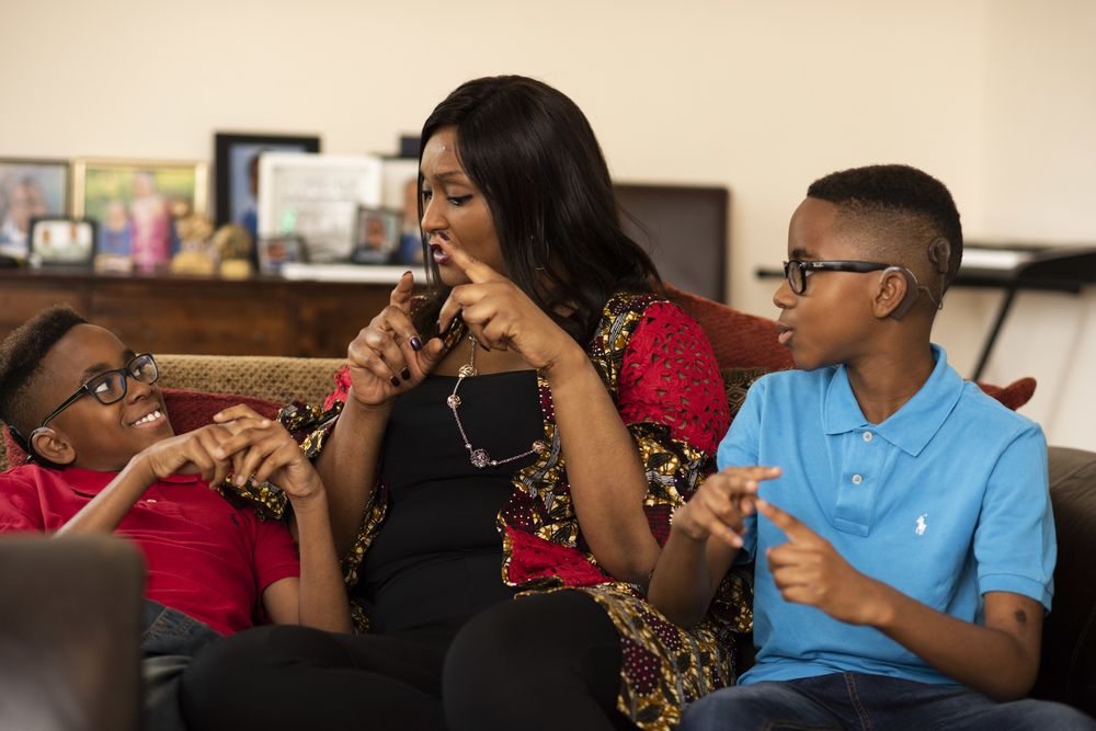 A photo of a woman and two children using sign language, courtesy of The National Deaf Children's Society