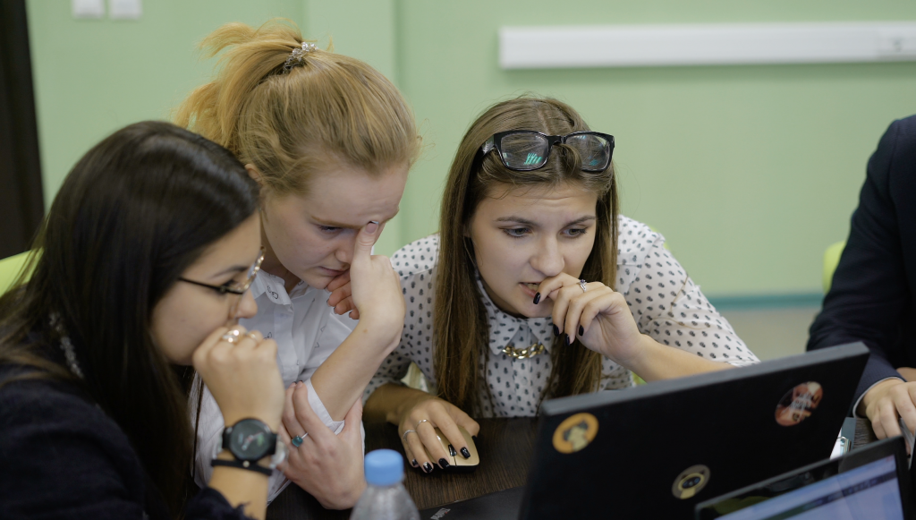 Group of students working at a laptop together