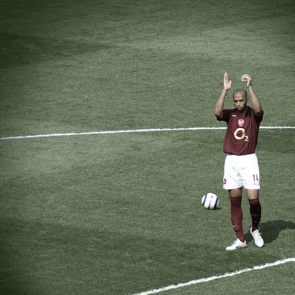 Thierry Henry, in a faded brown Arsenal jersey, on the football pitch, saying farewell to the crowd by applauding them after his last game for the team.