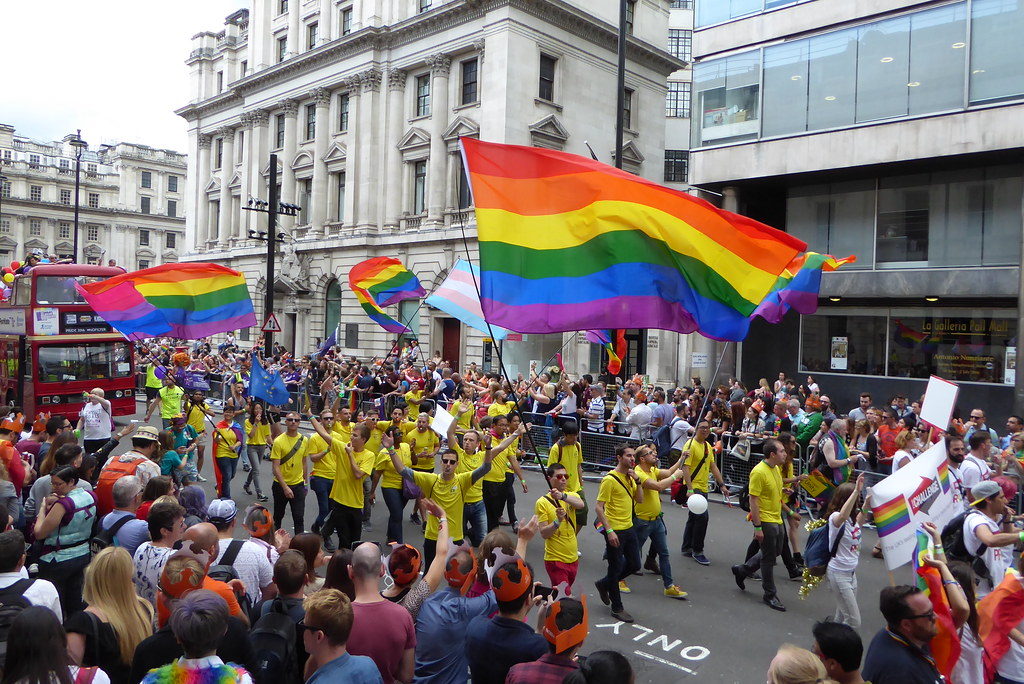 People on the streets marching waving rainbow flags