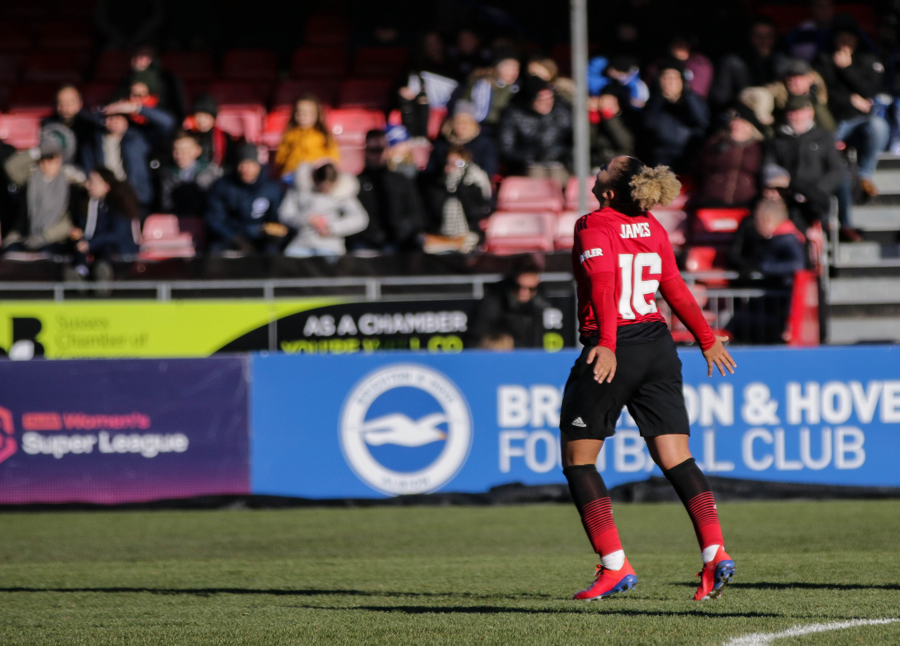 Lauren James in a Manchester United red jersey celebrating in front of a crowd after a goal.