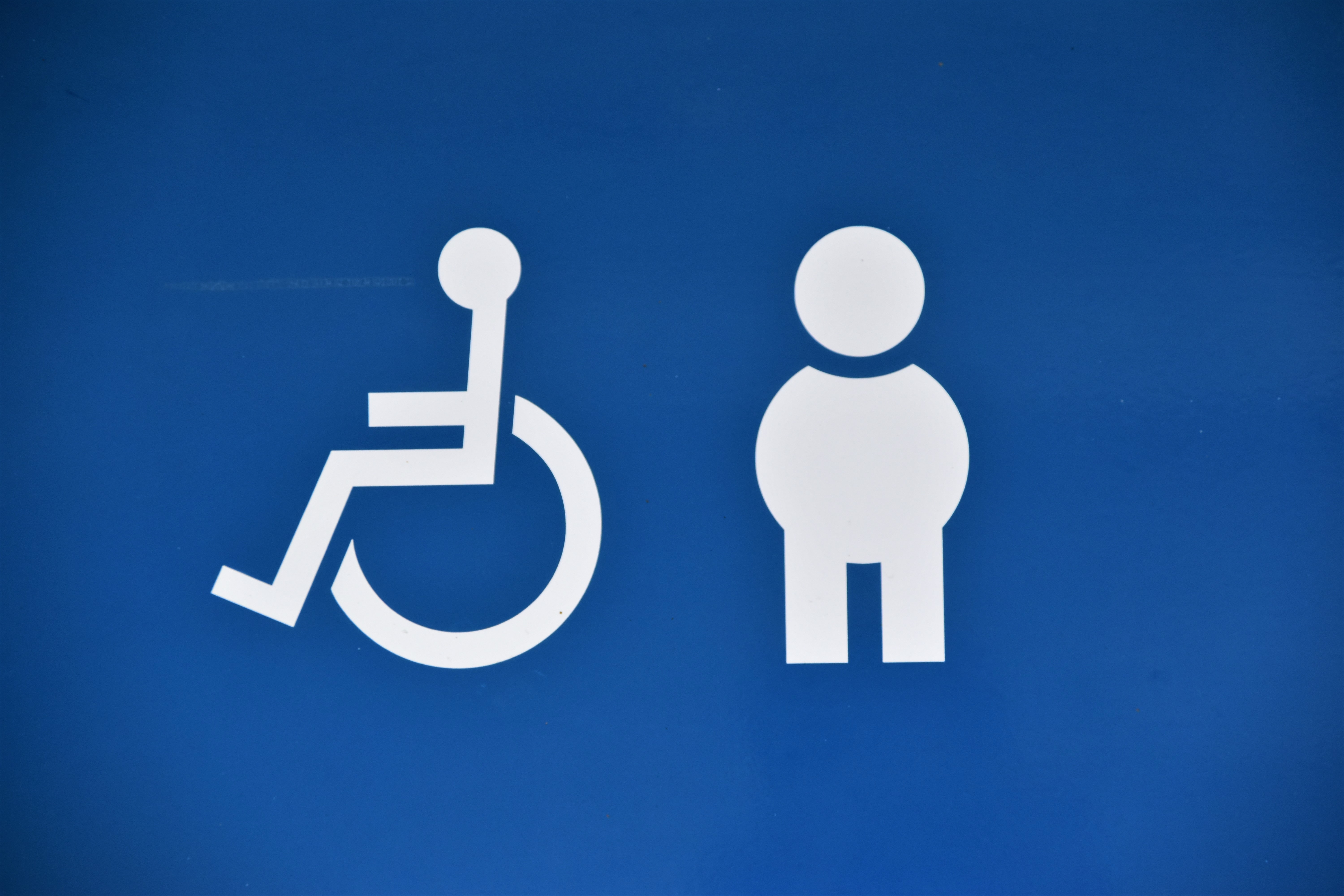 The symbol for a wheelchair user and a stick figure drawn in white sit on a blue background. The illustration represents visible and invisible disabilities.