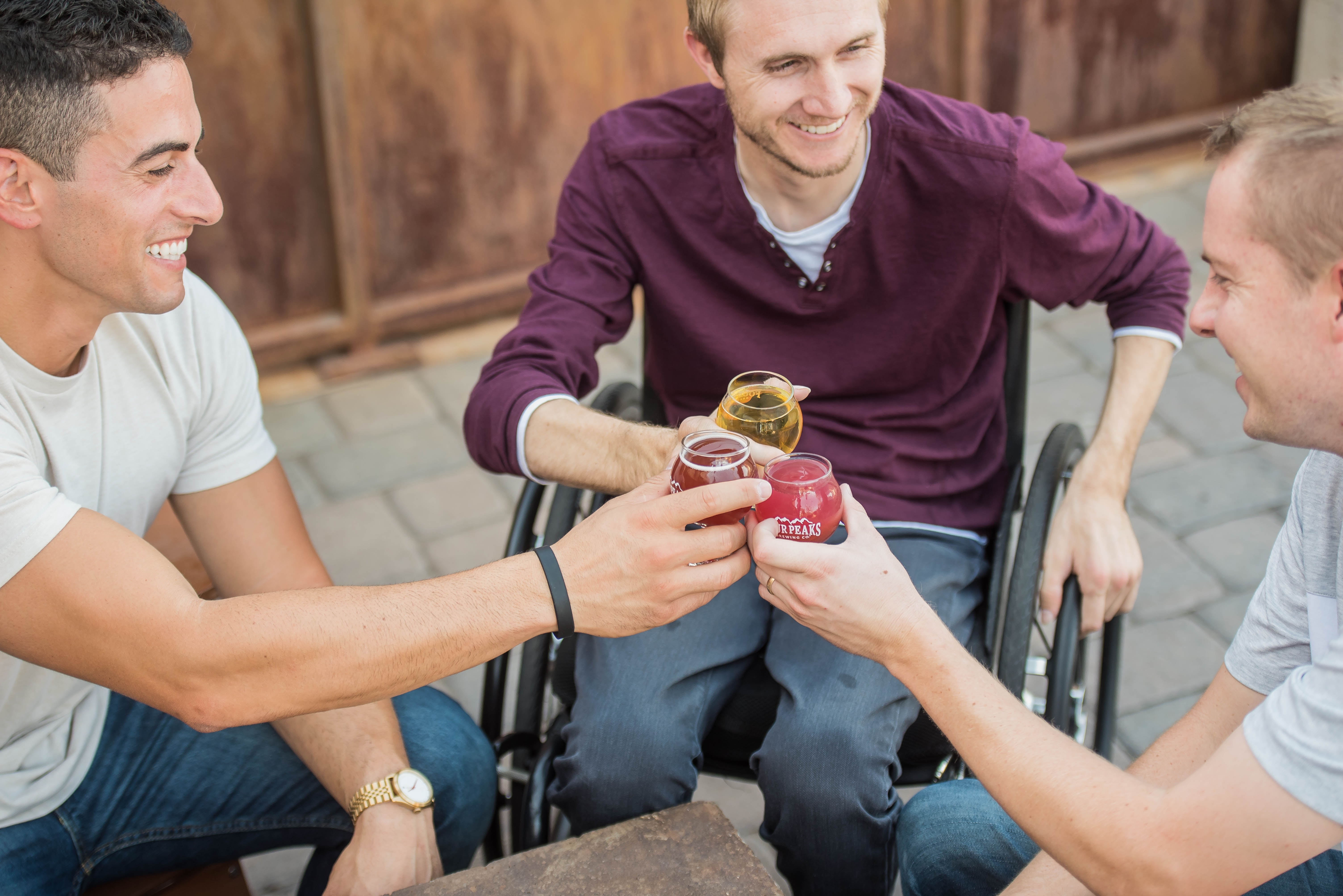 A group of three men chink glasses outside at a pub. The man in the middle, wearing a dark purple t-shirt and jeans, is a wheelchair user.