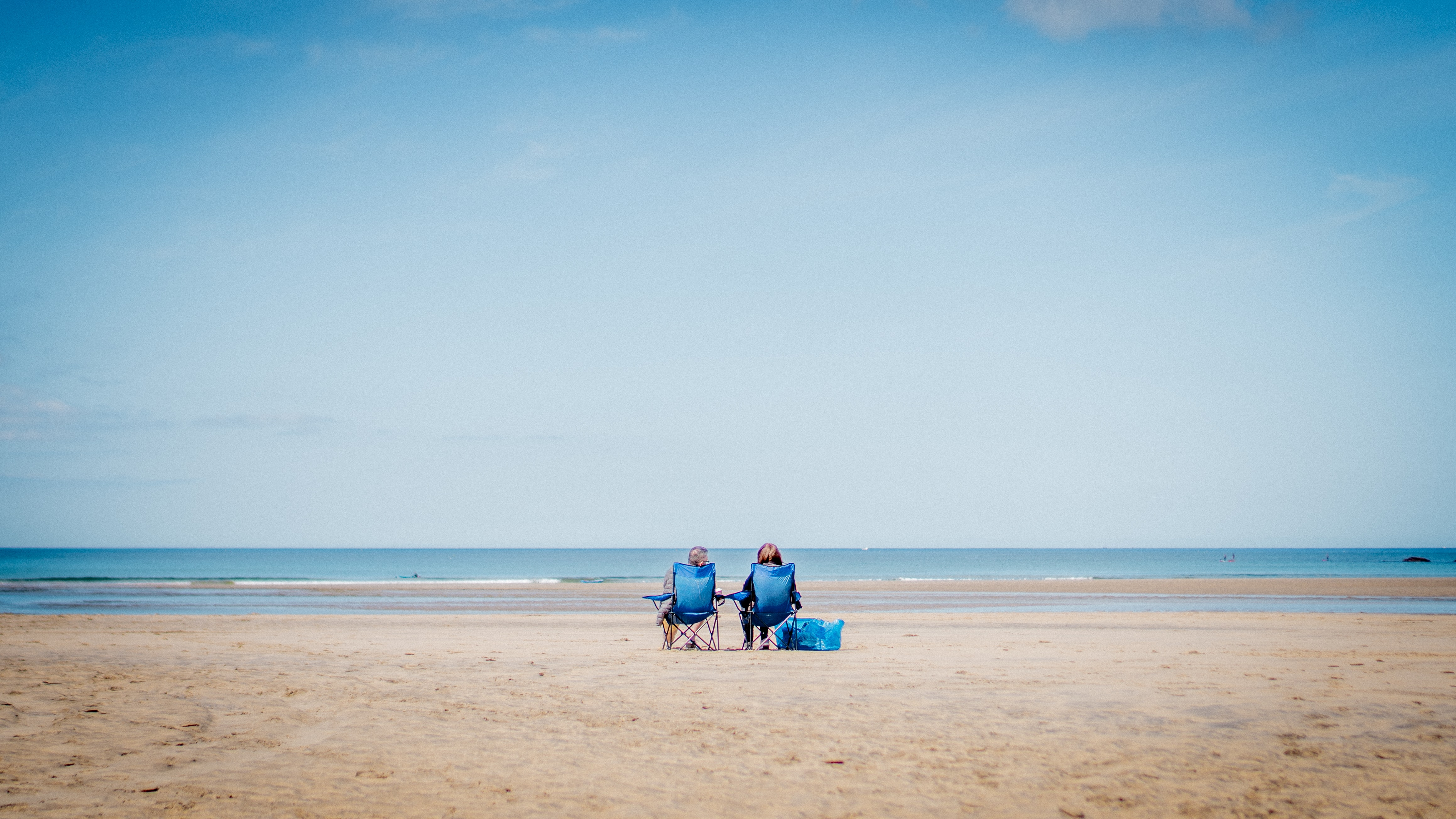 A couple sit on beach chairs on Gwithian Beach in Cornwall