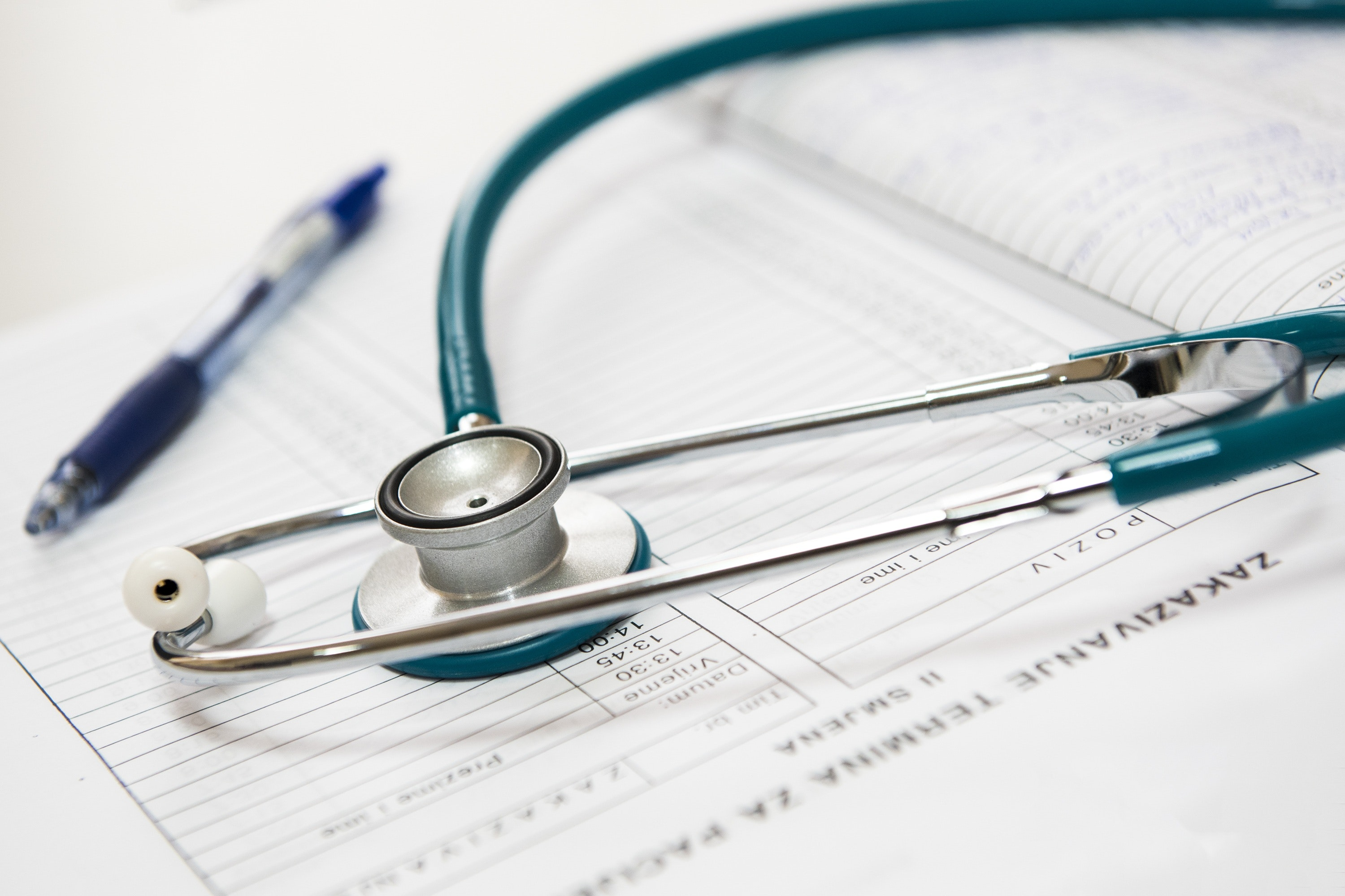 An empty information sheet lies underneath a pen and a stethoscope.