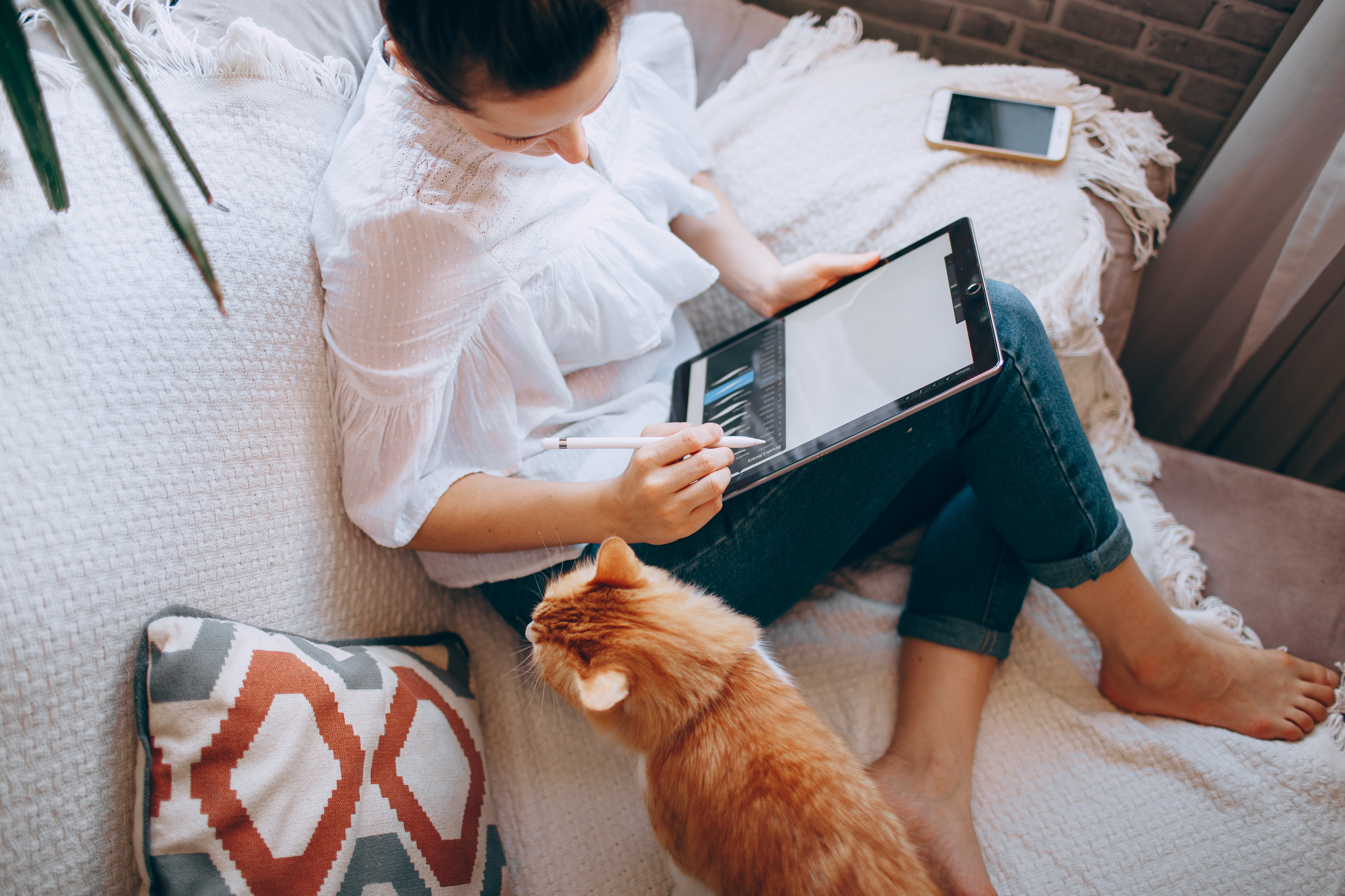 A person works on their tablet on the sofa with a ginger cat next to them