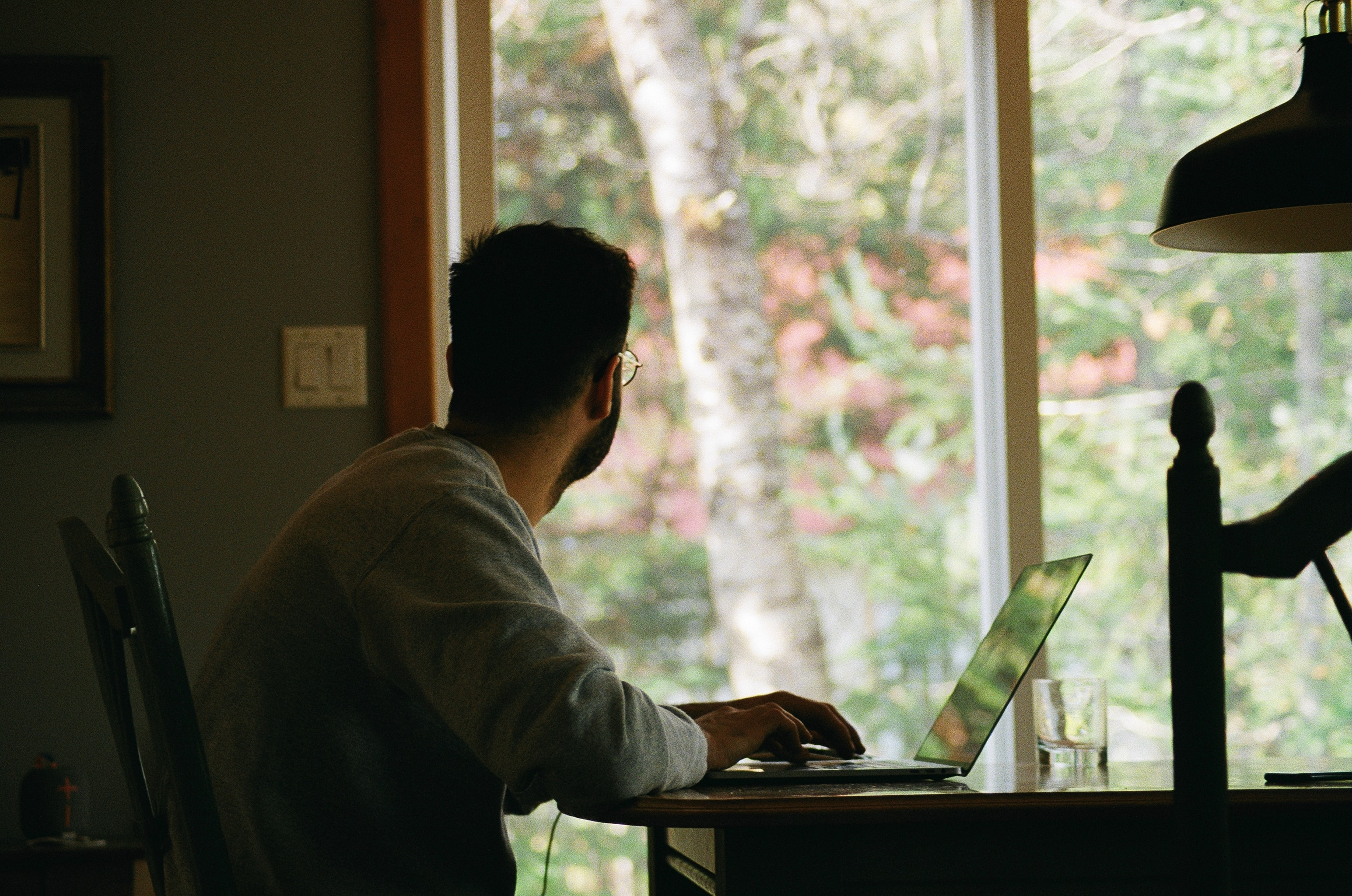 A man looks out the window while working on a laptop at home