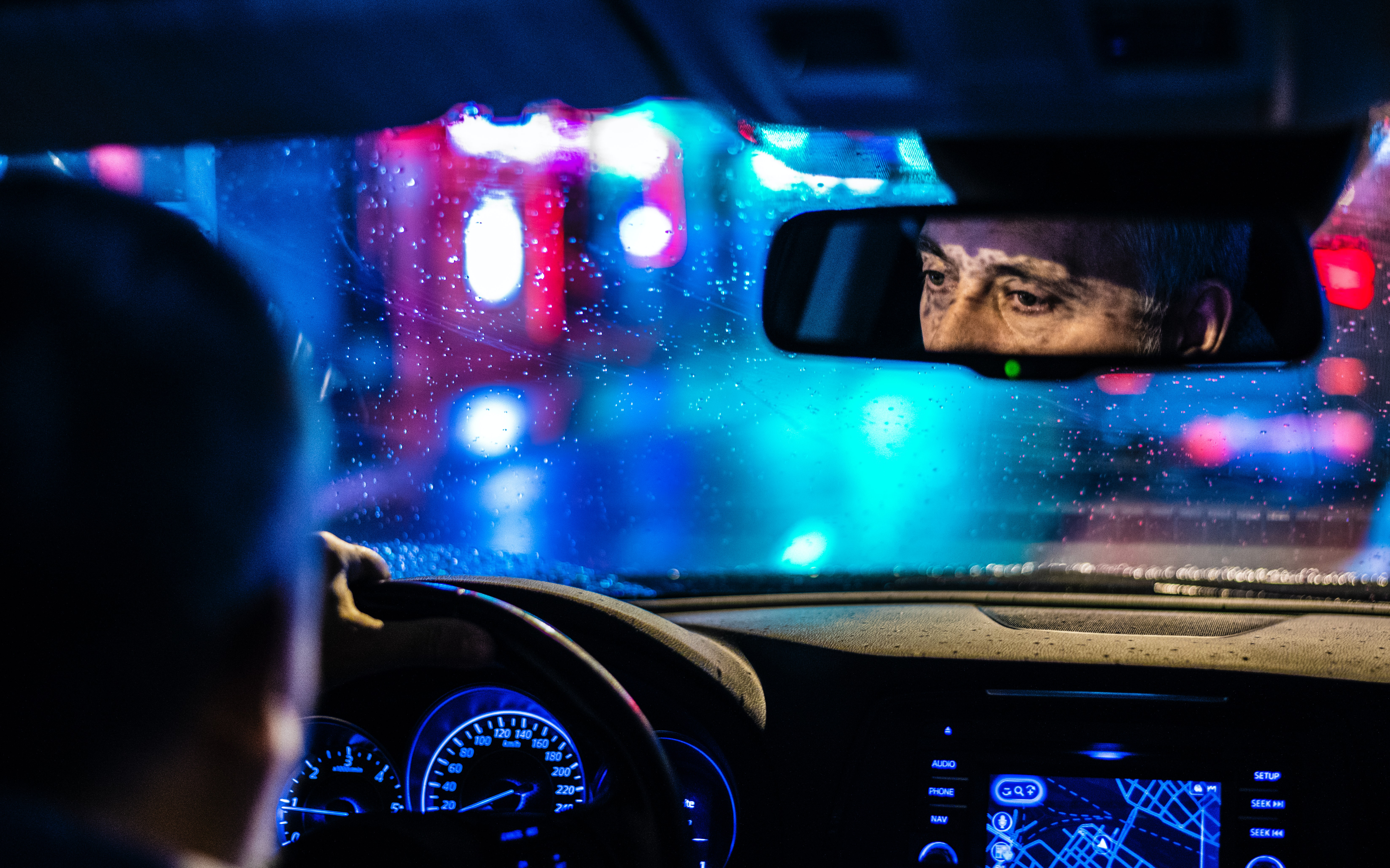 A photo from the back seat of a taxi shows the reflection of an uber driver's face in the mirror while he drives at night.