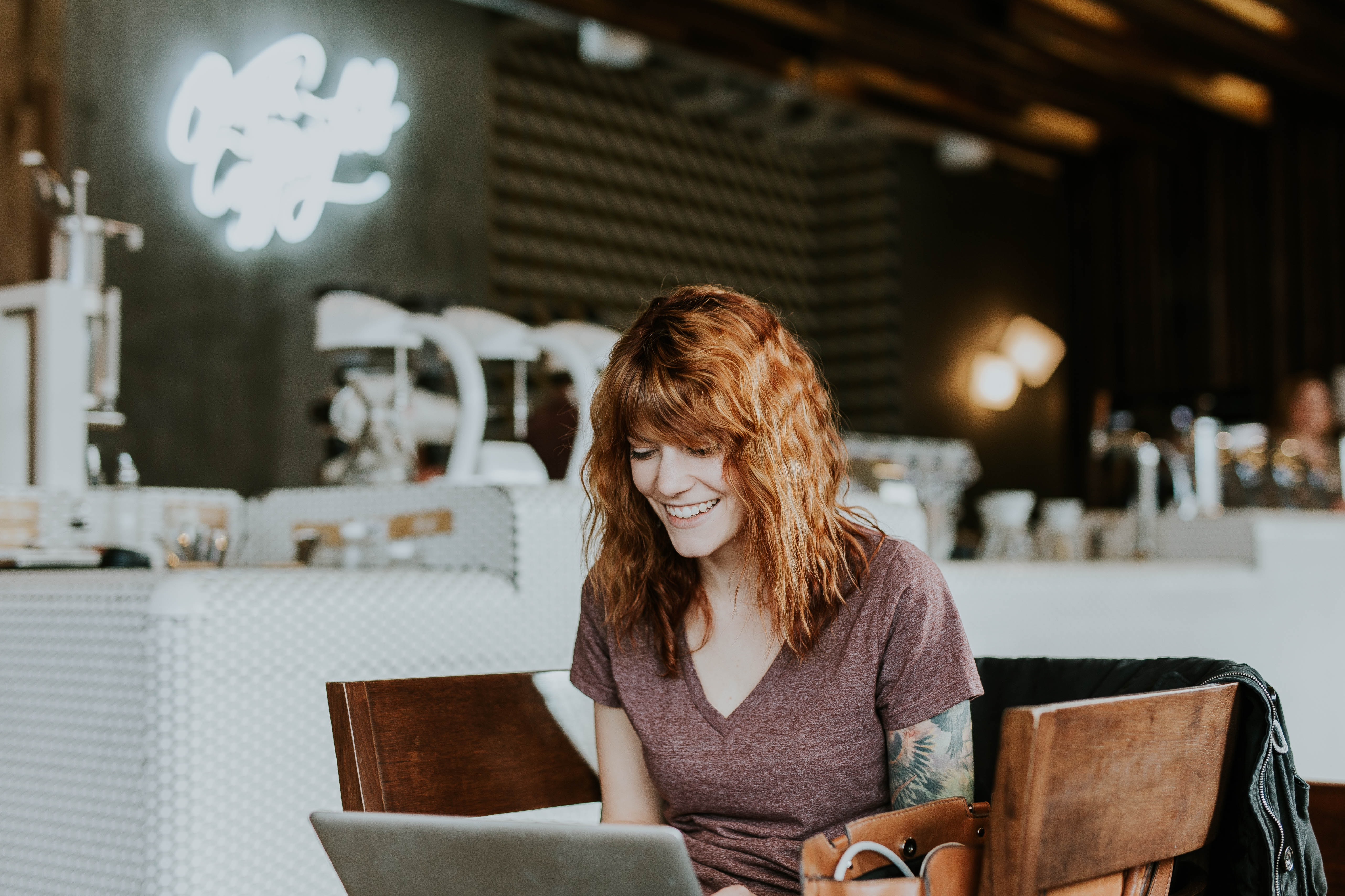 A red-headed woman smiles while working on her laptop in a cafe.