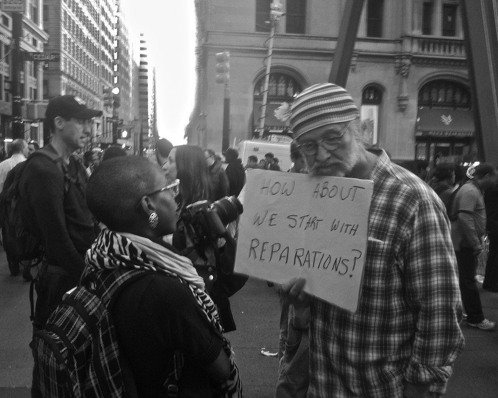 A man holding a sign saying ;how about we start with reparations?'