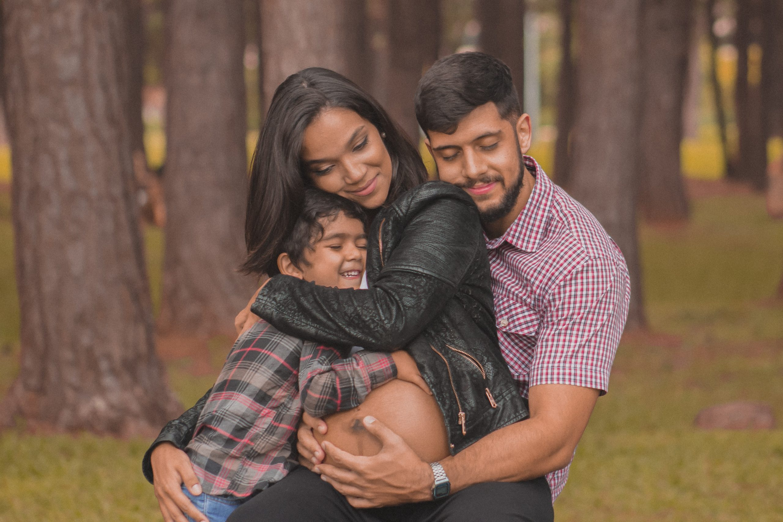 A family of a man, pregnant woman, young son embrace each other in the woods.