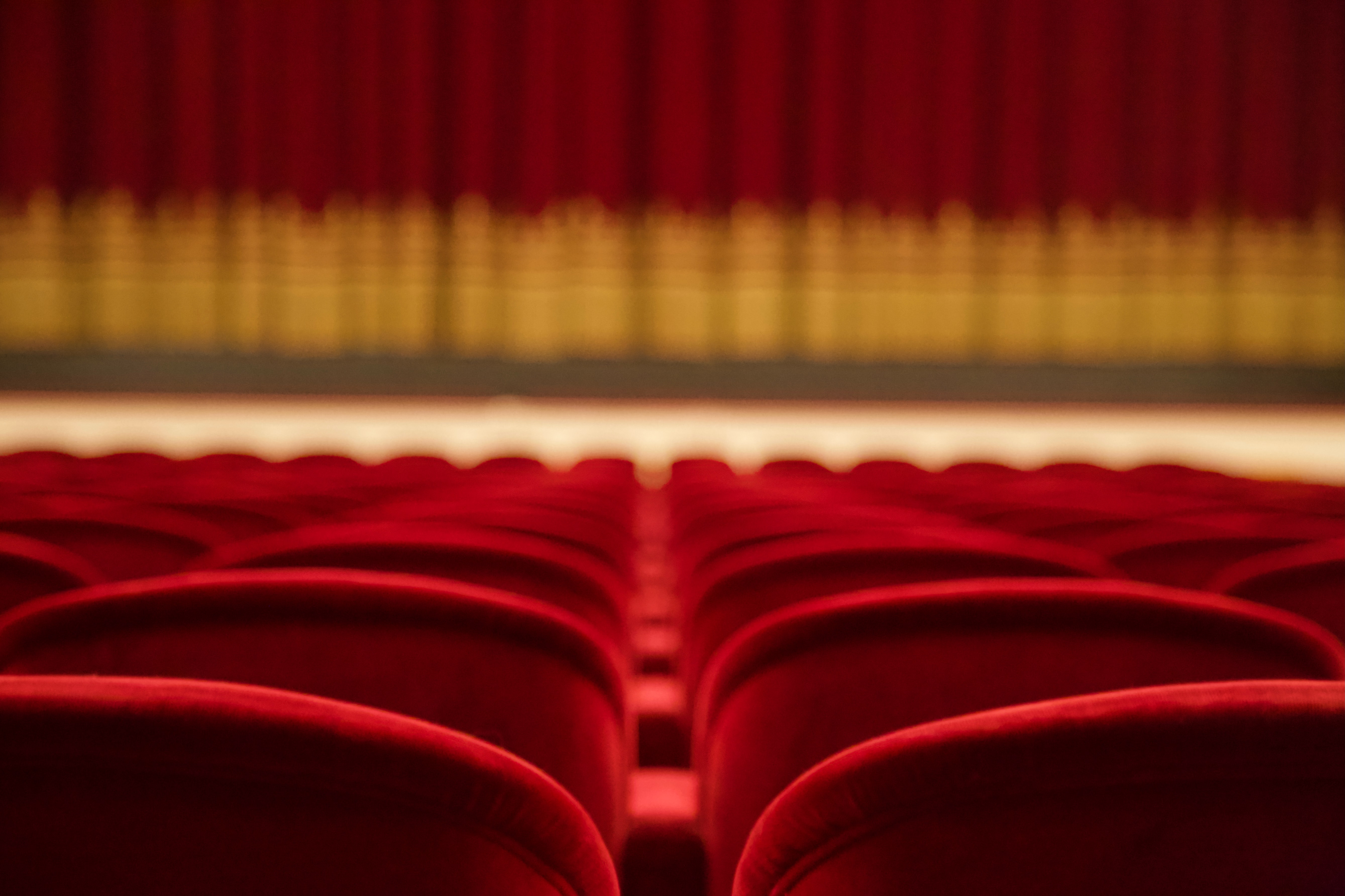 a close p shot of red theatre chairs shows the theatre curtain blurred in the forefront of the image