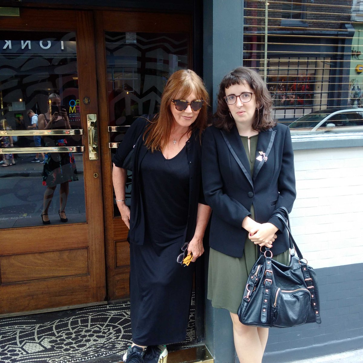 Two white women stand outside a blue building with a brown door. The woman on the left wears a black dress with dyed brunette hair. The younger, on the right, wears a green dress, black blazer, and holds a black bag on her left arm.