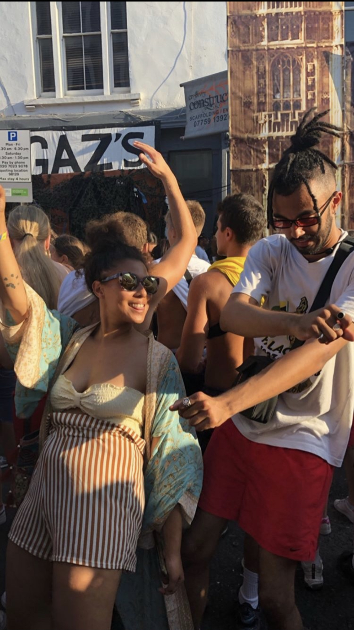 A young female person of colour stands at the front of a Notting Hill Carnival crowd, dancing with her brother.