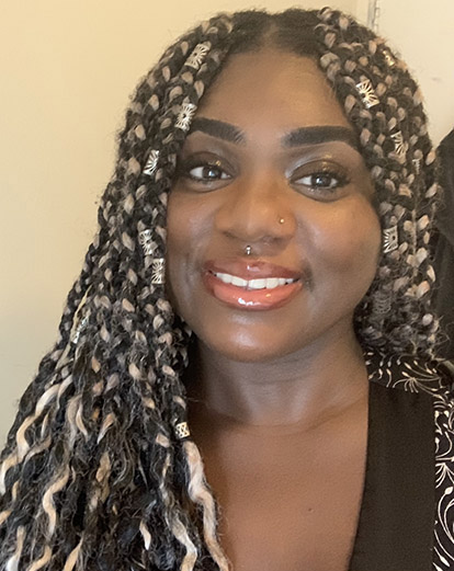 Head and shoulders shot of a young Black woman with blonde and dark plaits. She is smiling.