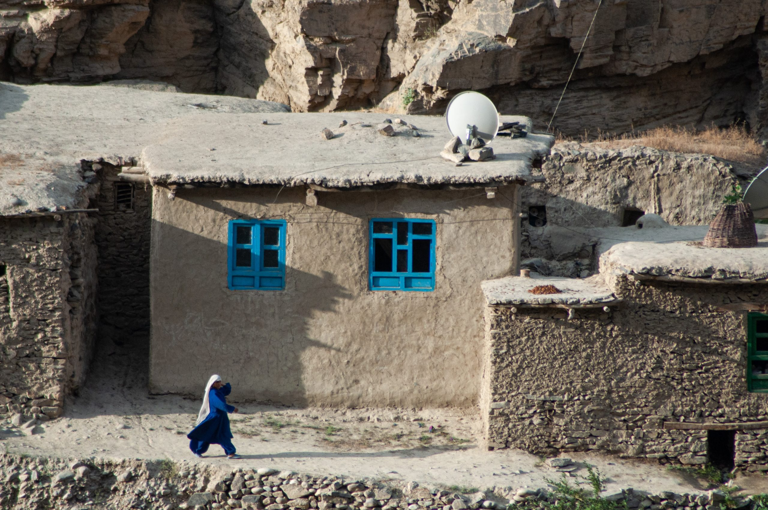 A women walks in front of a house in Afghanistan.
