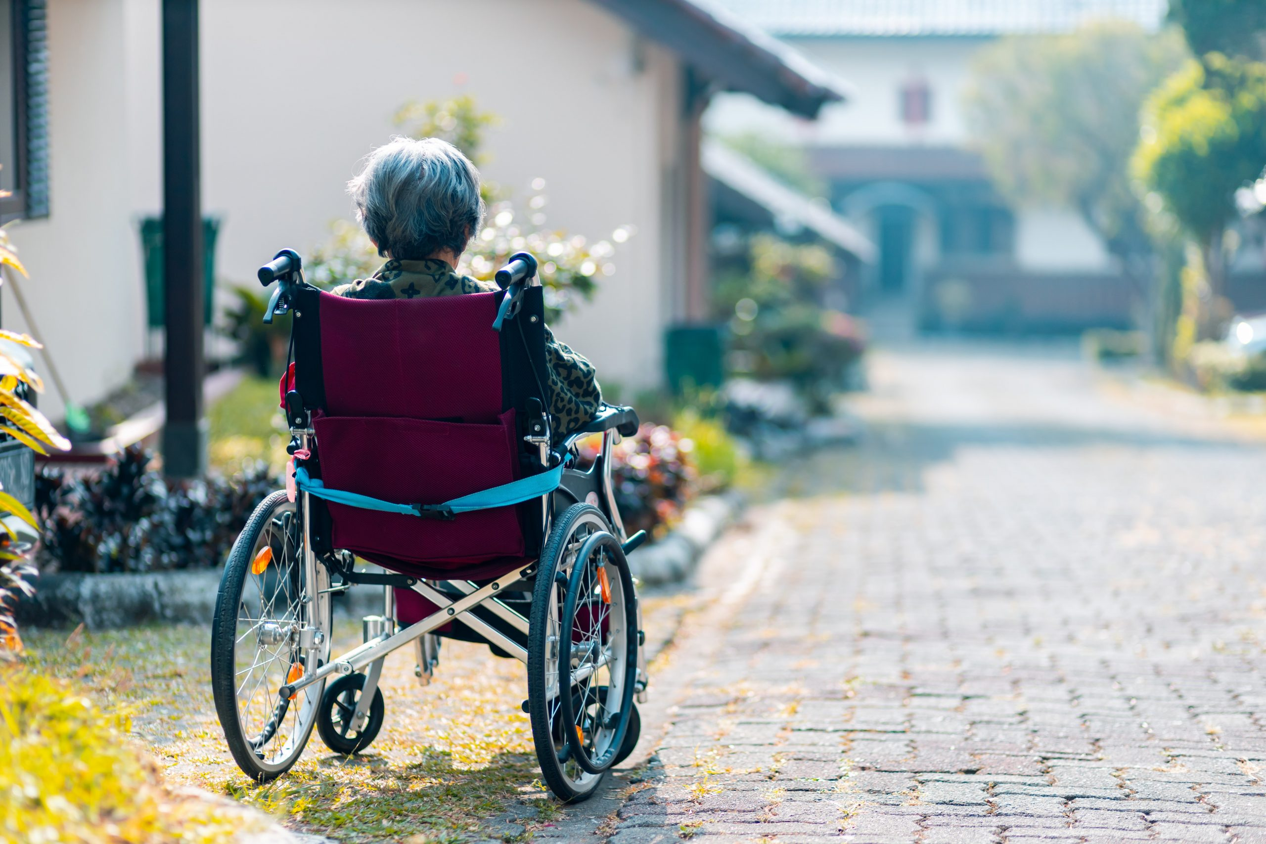 A person using a wheelchair faces away from the camera. Their wheelchair has a red seat and they are facing outward toward a road with a white house in the background.