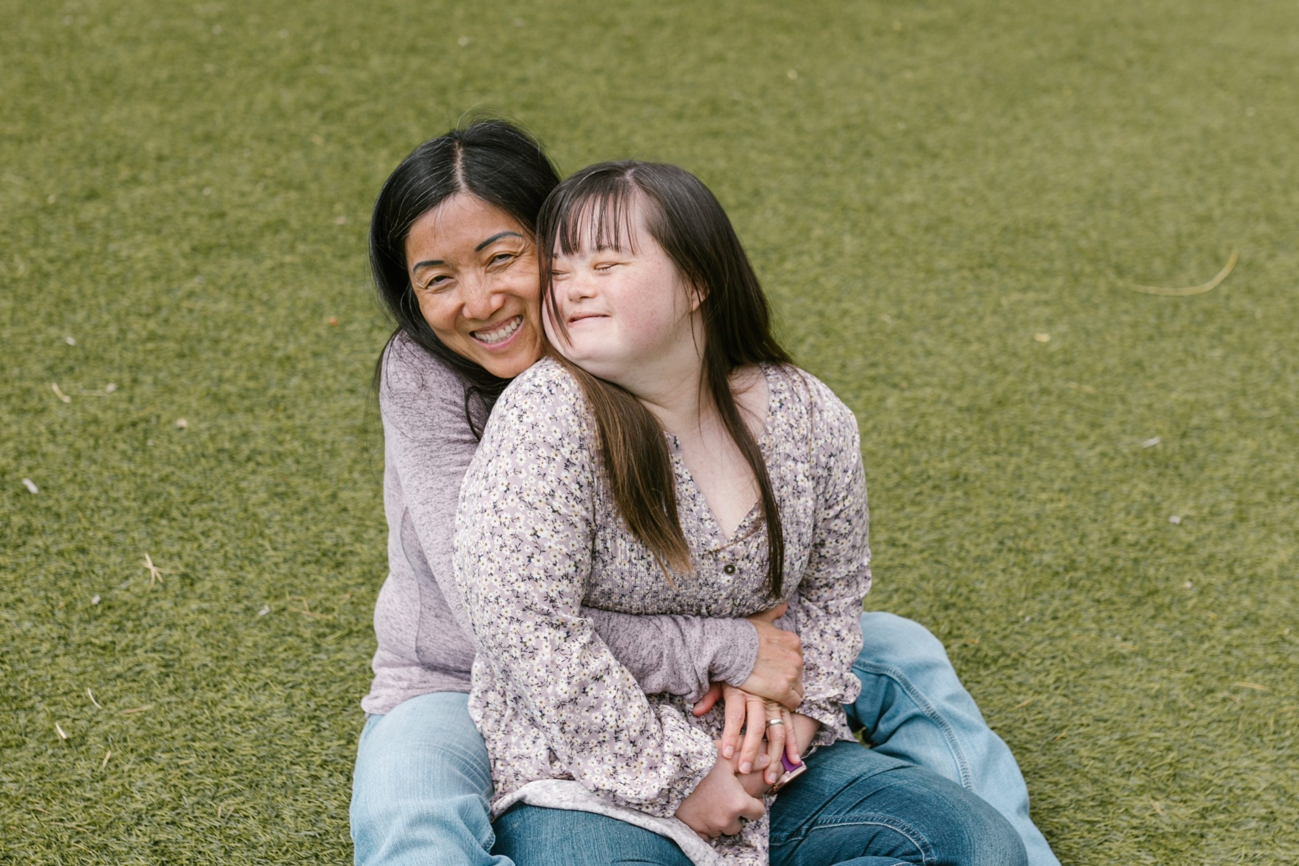 A woman with down syndrome sits on the grass wearing a long-sleeved top and jeans while a friend hugs her from behind.