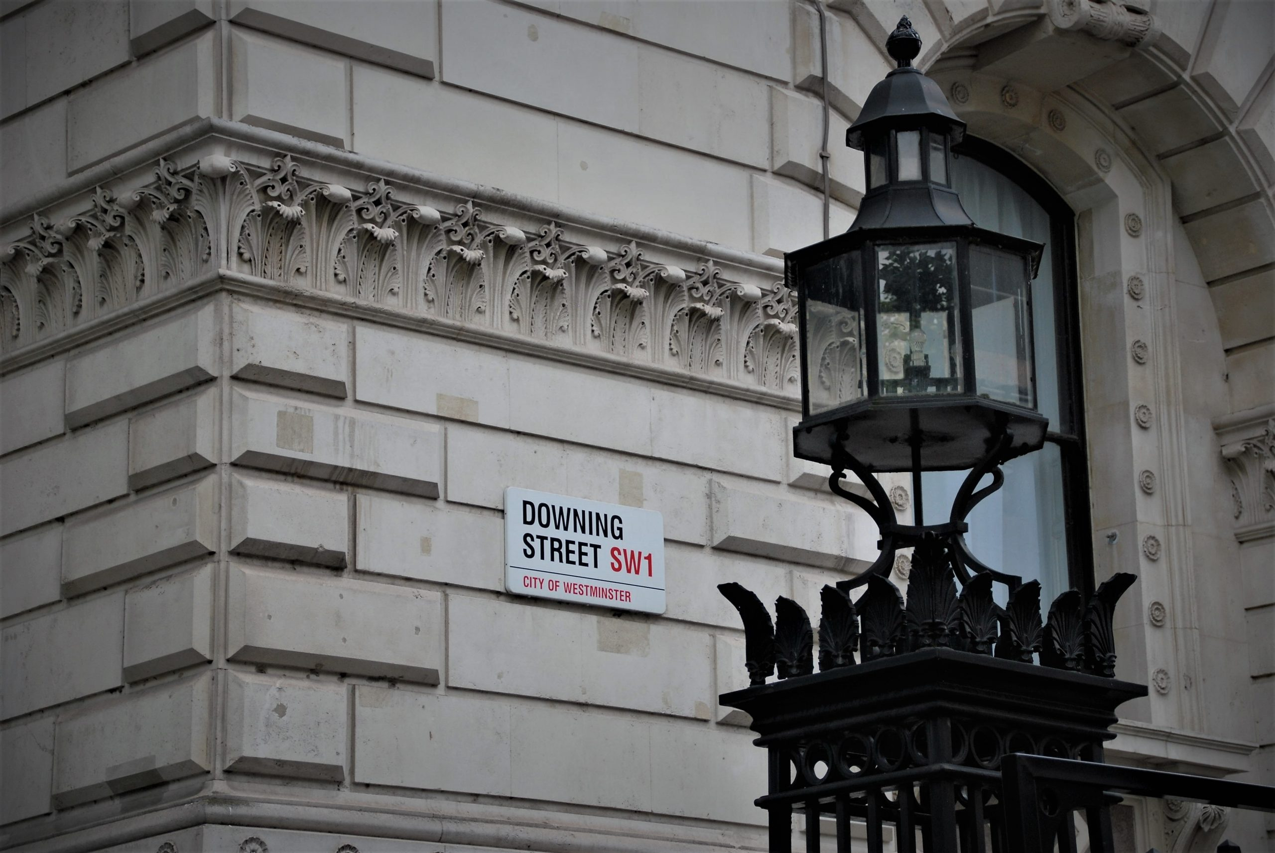 The photo shows a black street lamp in the foreground. In the background, there is a sign for Downing Street.