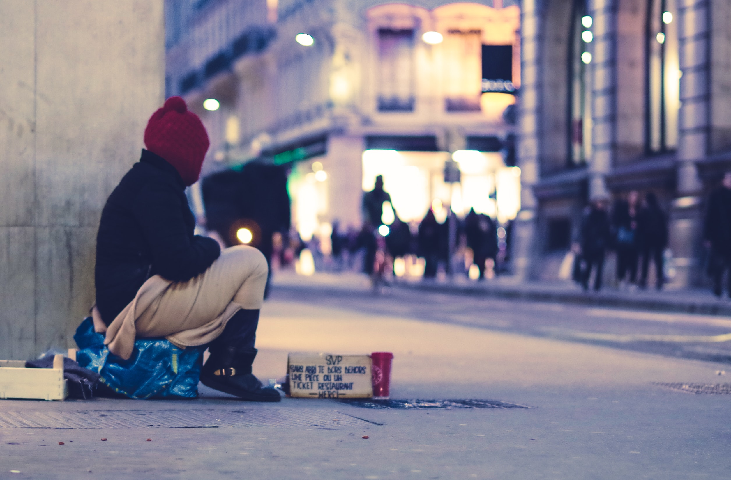 A homeless person sits on their belongings. They are wrapped up in a hoodie and are looking at into the street.