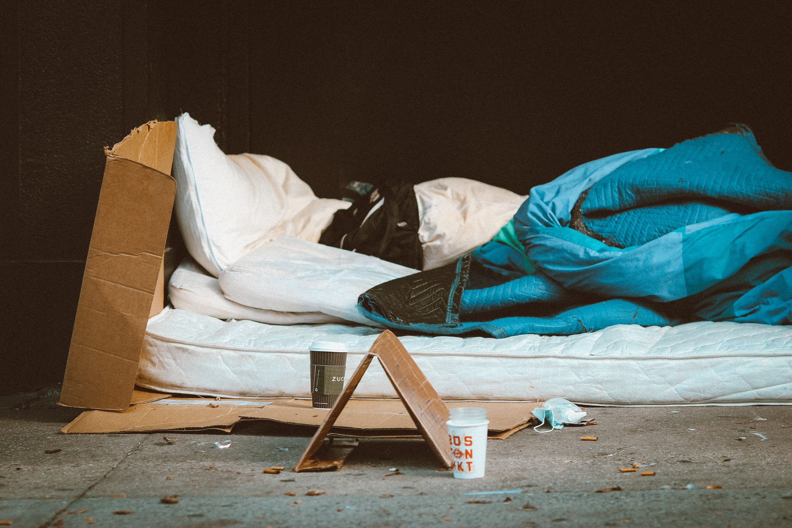 A homeless person sleeps on a mattress out in the open. A cardboard sign is next to them and they are wrapped in a blue sleeping bag.