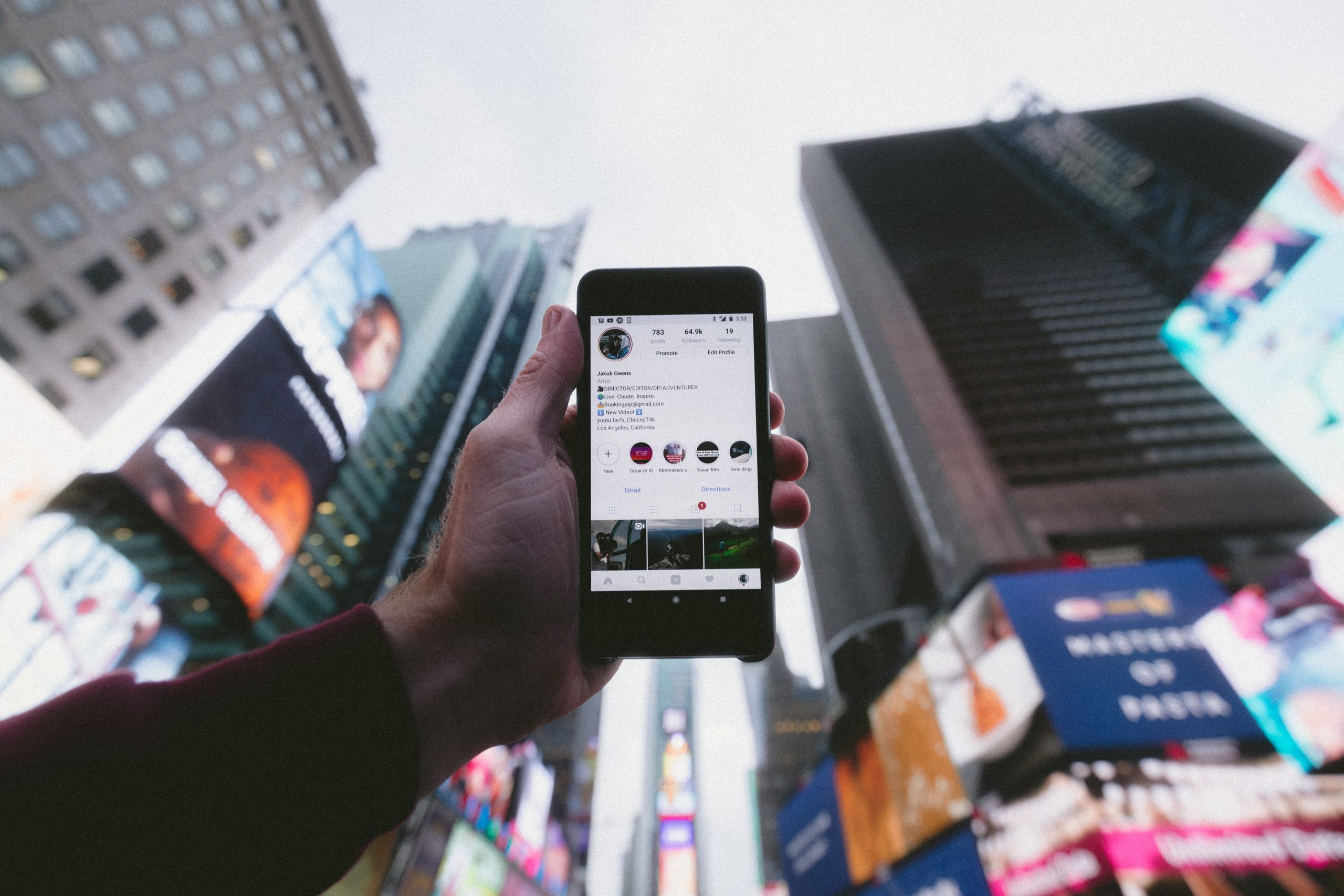 A person holds up a mobile phone against a backdrop of skyscrapers.