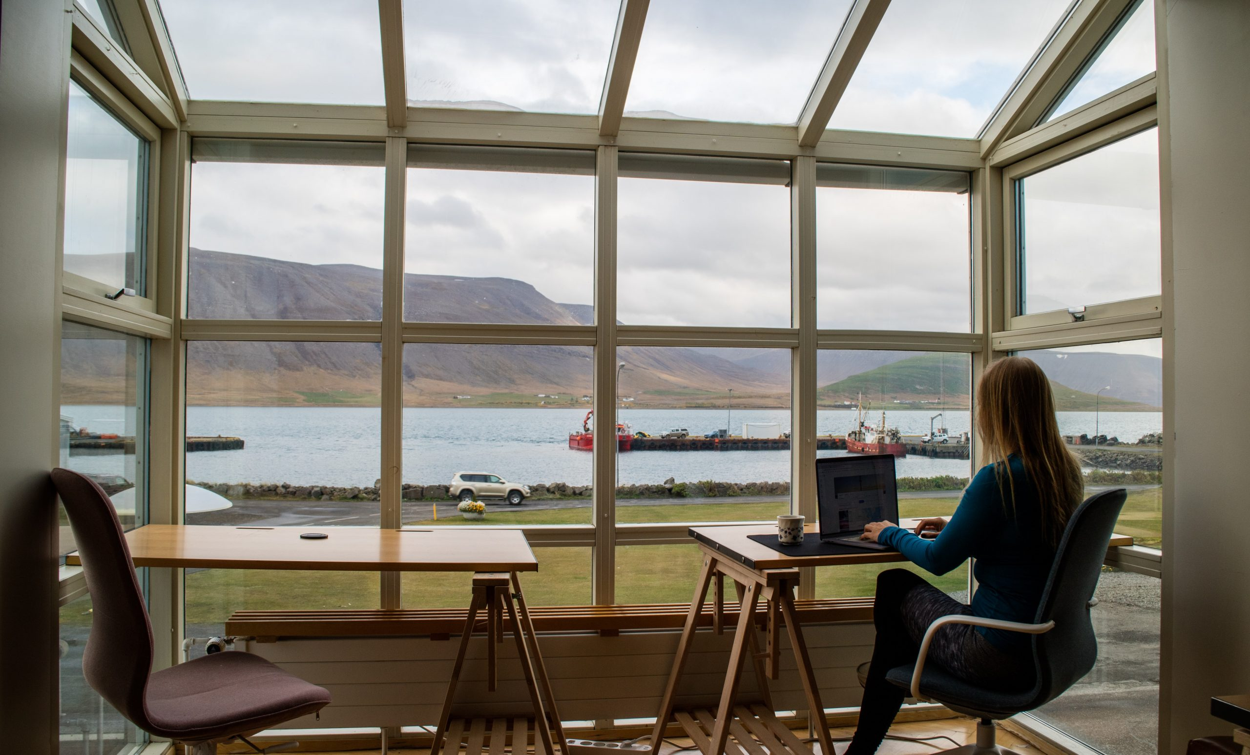 A white woman sits in a conservatory extension, looking out to sea and the beach. She is sat at a small wooden desk with a MacBook computer on top.