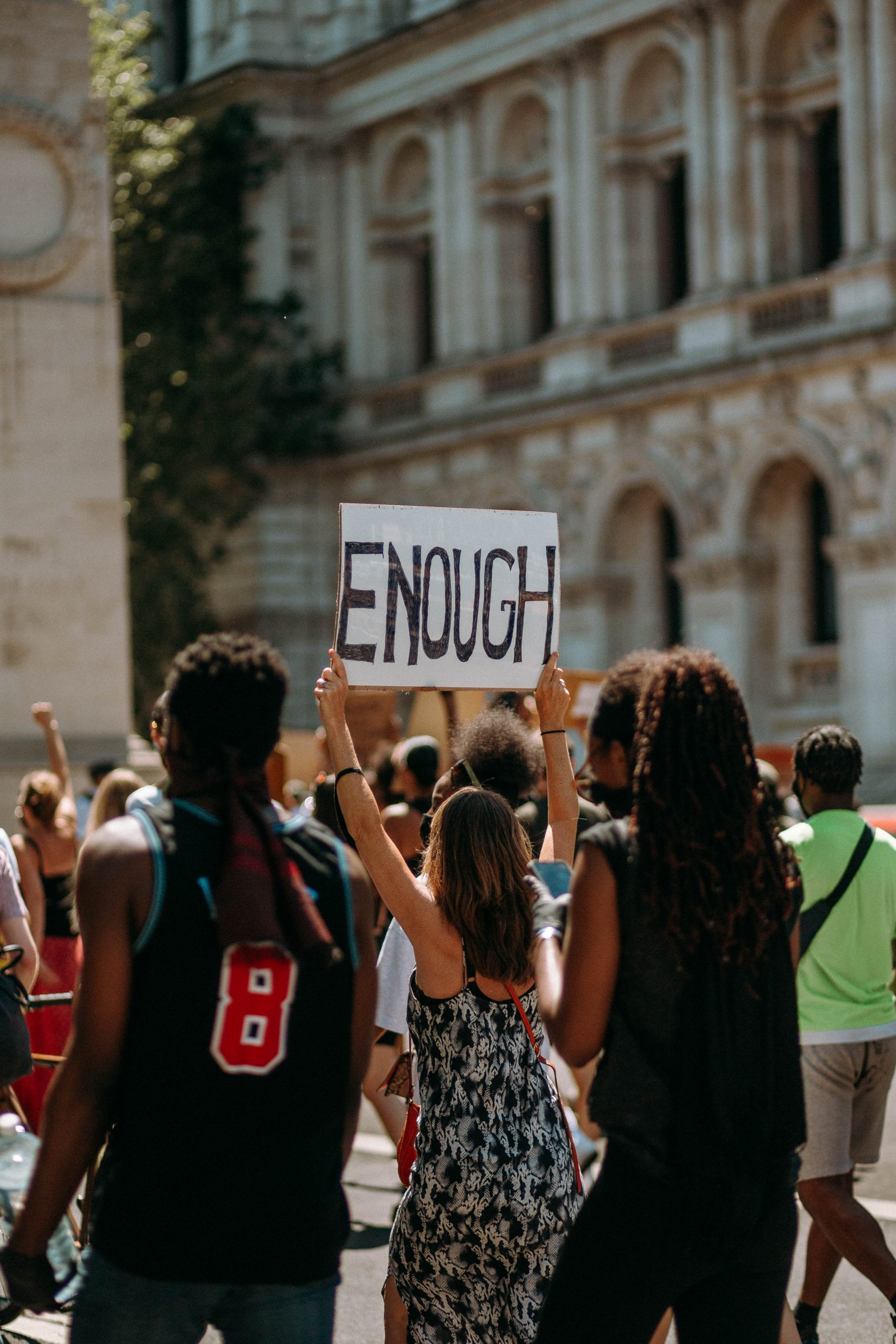 A crowd protests in London; a woman of colour stands with her back to the camera, holding a capitalised sign reading ENOUGH