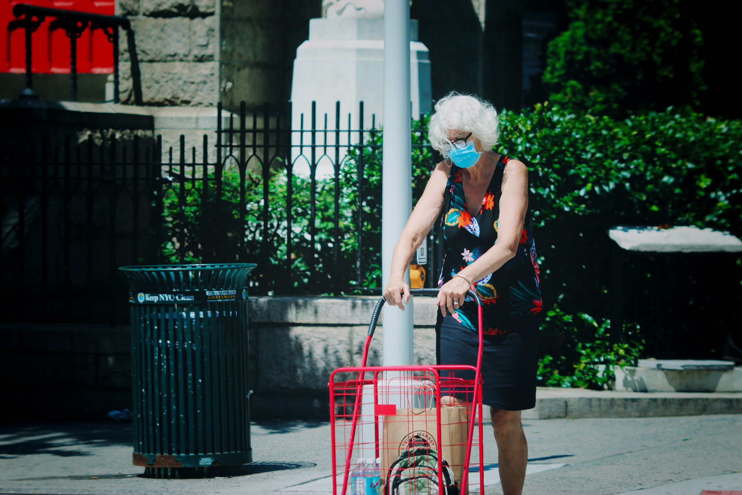 An elderly, white-haired woman walks down the street with her shopping trolley on wheels. She is wearing a disposable light blue mask.