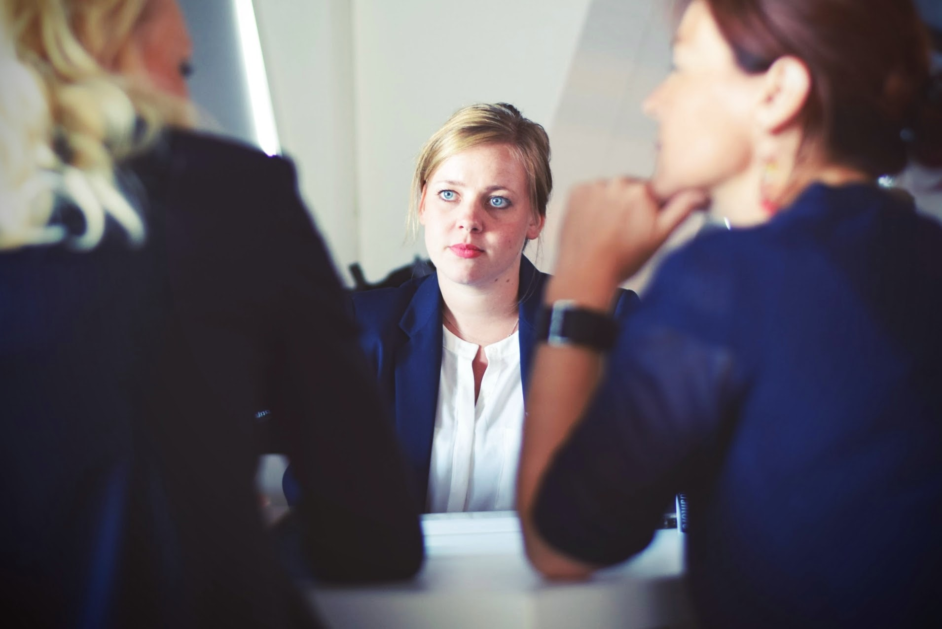 A white woman sits at a table in the centre of the frame. Two people are speaking to her with their backs to the camera from the other side of the table.