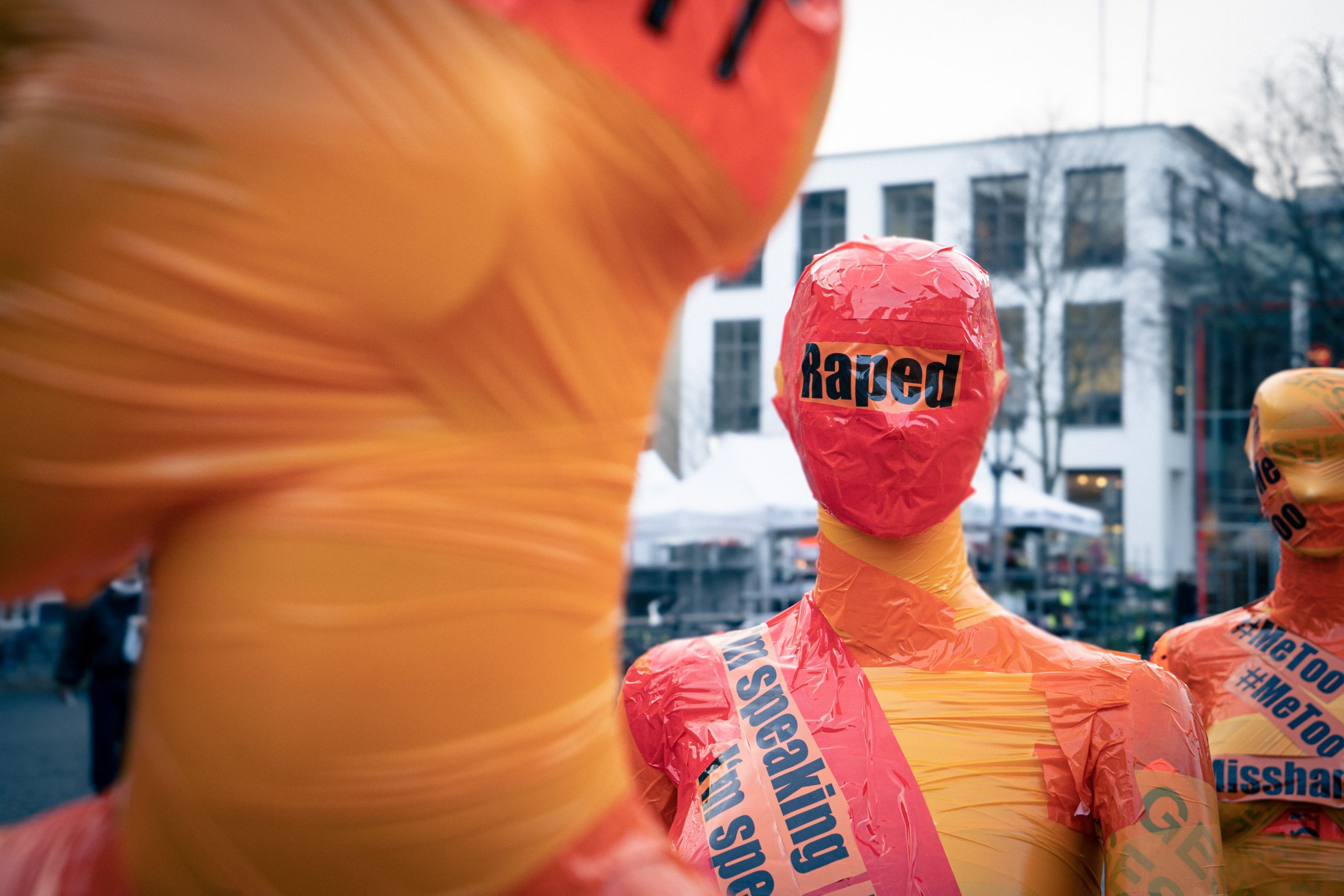 """A dumy is wrapped in orange and red tape with the word """"rape"""" in stark black letters across its face."""