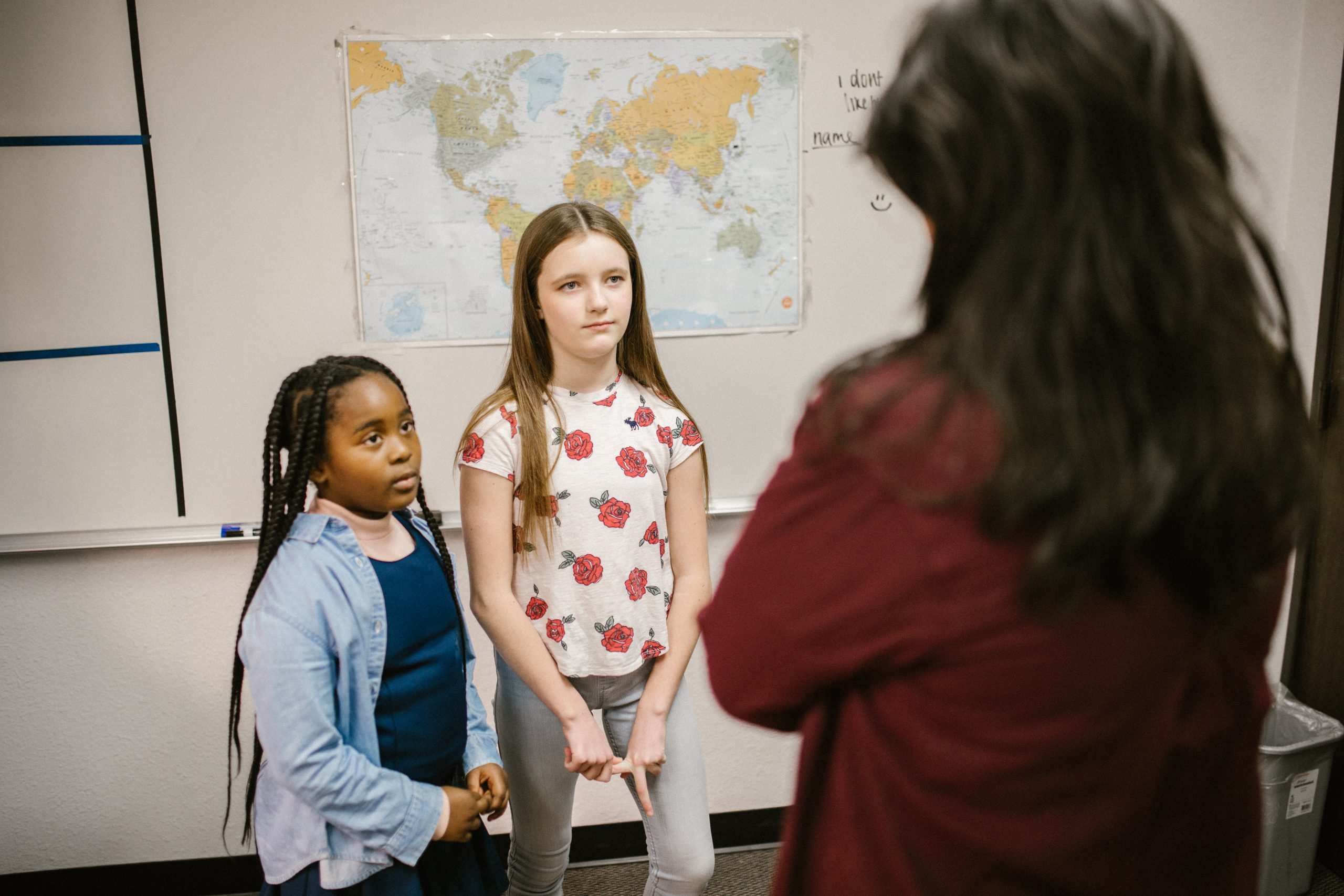 Two young students speak to a teacher
