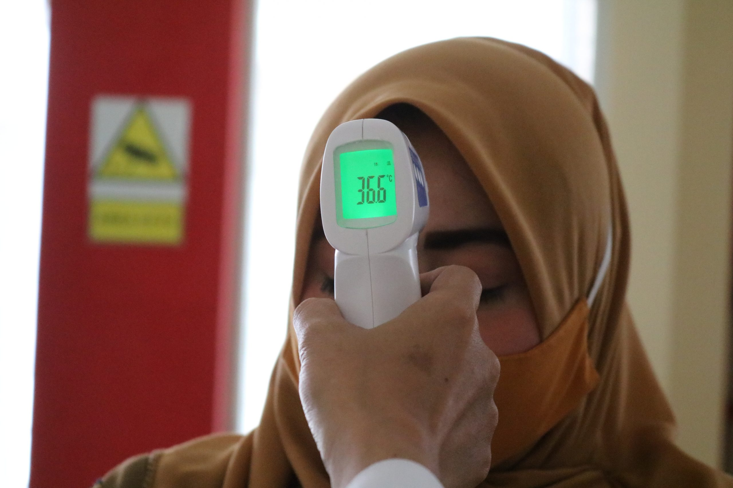 A woman wearing a light brown hijab and a face mask has a temperature taken.