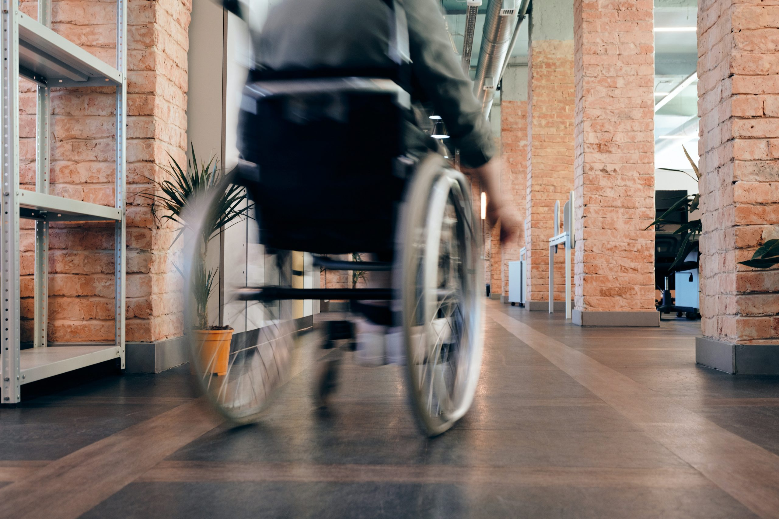A wheelchair user moves away from the camera in a light blur. They are inside a building with brick walls.